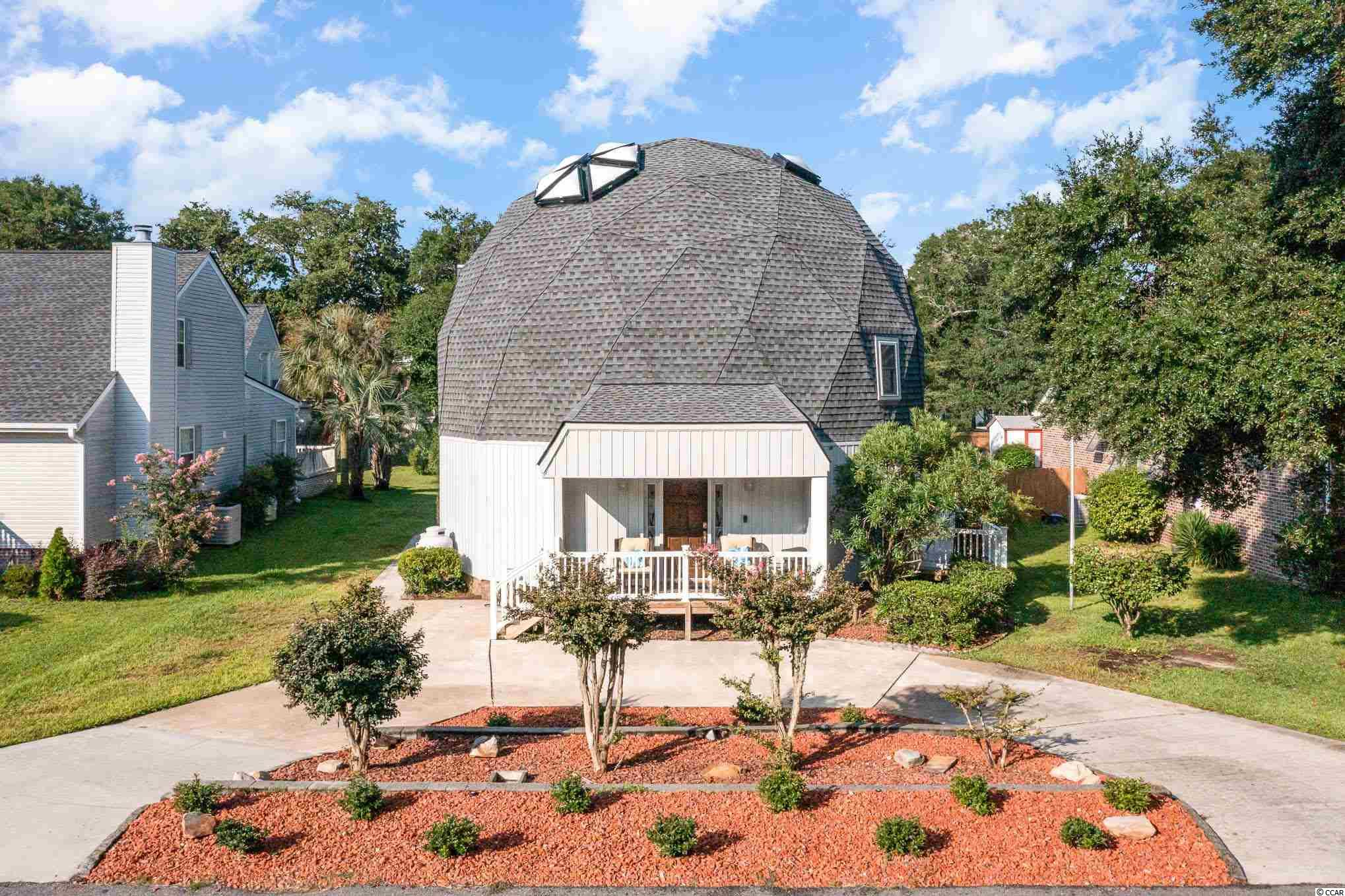Here's an opportunity to own this unique, geodesic dome home just a few blocks from the beach! The home has a perfect layout, and the unique structure grants it a spacious, airy feel. Aside from the aesthetic attributes of the geodesic dome, it also is 30% more efficient over a conventional home of a similar size. Construction also withstands all kinds of inclement weather- be it hurricanes, earthquakes or tornados As you enter, you're greeted by high ceilings. The living room is equipped with a fireplace, perfect to gather round with friends and family. Continue onto the dining area and kitchen. The kitchen boasts granite counters, backsplash, a large pantry, and all the appliances you could need. Towards the back of the home, a spacious utility room where your washer and dryer are located. Also, a full bathroom and main level room that currently serves as a home office, but could also serve as a bedroom. On the second floor, you have the spacious primary bedroom complete with dual closets as well as an additional bedroom. On the top floor, you a skylight greets you on the landing, where you can appreciate the beauty of the dome. Two additional bedrooms each with dedicated closets are also located on this top floor. With hardwood floors throughout the common areas and stairs, this home is turnkey and ready for you to make it your own. Out back, a large deck complete with a hot tub is the perfect place to entertain, or relax after a long day. Come take a look today!