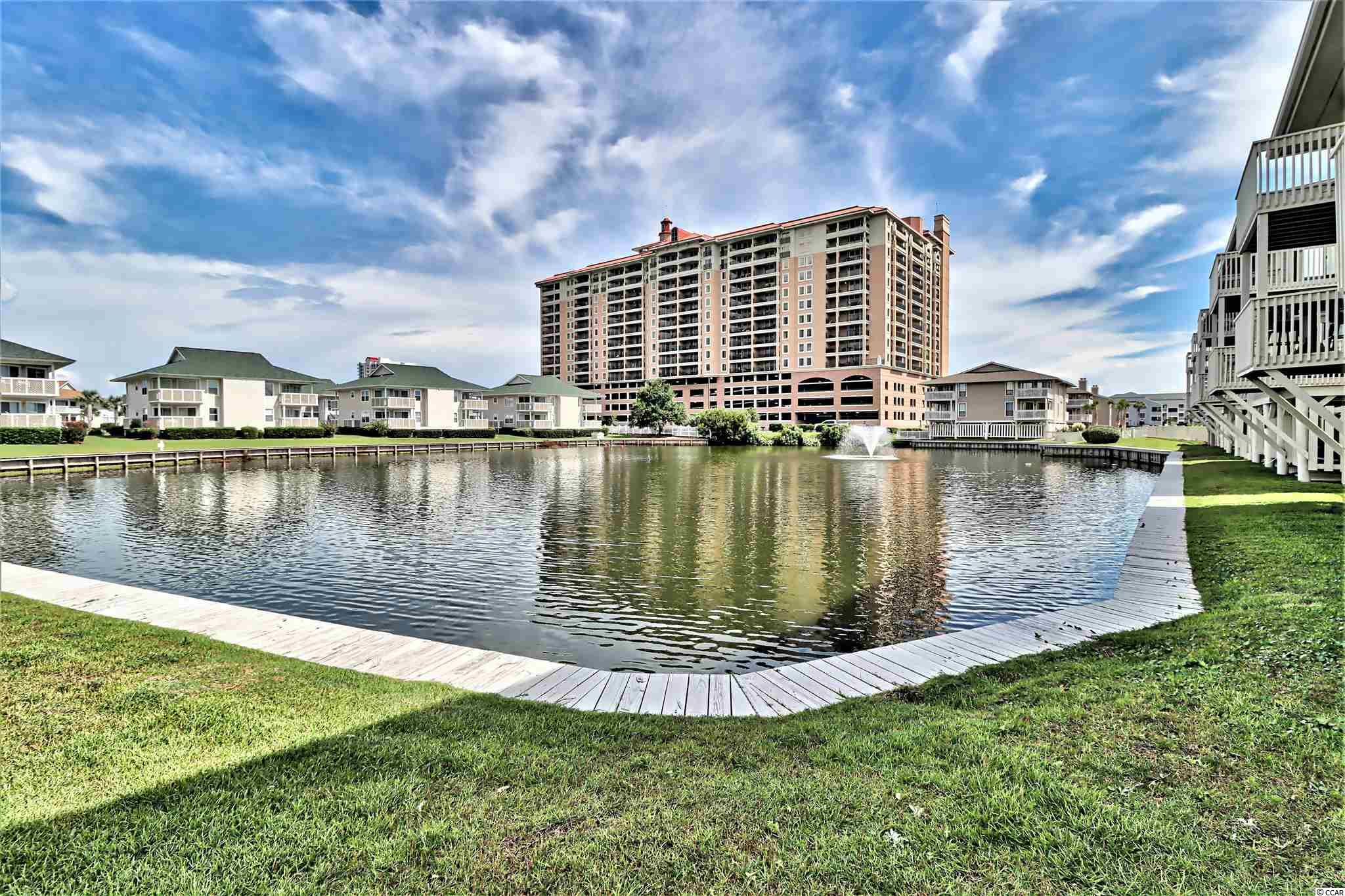 Great opportunity to get into one of North Myrtle Beach's most popular 2nd row luxury high rise resorts. Tilghman Beach and Golf Resort is located directly across the street from a major city beach access and crosswalk. The building features an abundance of both indoor and outdoor amenities that appeal to today's vacationers, families and guests. Heated pools, hot-tubs, lazy river, exercise room, sauna, on-site bar and grill, huge sunning patio, children's water-play area.. the list is endless! Located in then heart of all the activity and fun at the beach, yet this updated condo offers owners and guests plenty of peace and serenity. Breath-taking views of a lake with lit fountain, the Surf Golf Club and golf courses may be enjoyed from the main living area of the condo as well as from a large balcony with access from both the master bedroom and living room. A gorgeous, tree-lined horizon melting into a blue sky in the distance sets the tone for a magical vacation and relaxation.