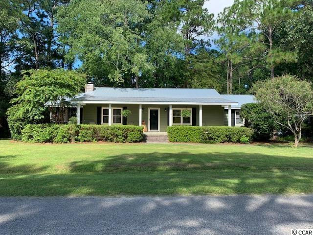 Located in the highly desireable Non HOA area of Hagley Estates, this 3 bedroom 2 bath home is convenient to both the Waccamaw River Boat Landing (Intercoastal Waterway) and beautiful Pawleys Island beaches. Updated with a metal roof, vinyl plank flooring and new HVAC in 2015, this classic home opens to a spacious living room complete with a vaulted ceiling and wood burning fireplace. Fireplace with old beam mantle provides a little ambiance and cozy comfort during the cooler winter months. Open dining area with full kitchen has plenty of counter and cupboard space. Master bedroom is spacious with a large walk in closet and attached private full bath.  Second bedroom includes an attached full bath with shared access from the 3rd bedroom located across the hall. All bedrooms and kitchen equipped with ceiling fans. Multiple porches include a covered screened porch off the dining area, a newly constructed deck off the back of the house, and front entry porch with room for numerous rockers. Yard is spacious with storage capacity for boats, golf carts and bikes... Central Pawleys Island location is convenient to schools, shopping restaurants, rivers and beaches. Historic Charleston is 70 miles south and Myrtle Beach attractions 30 miles north. Great opportunity as a full time, part time or investment property!