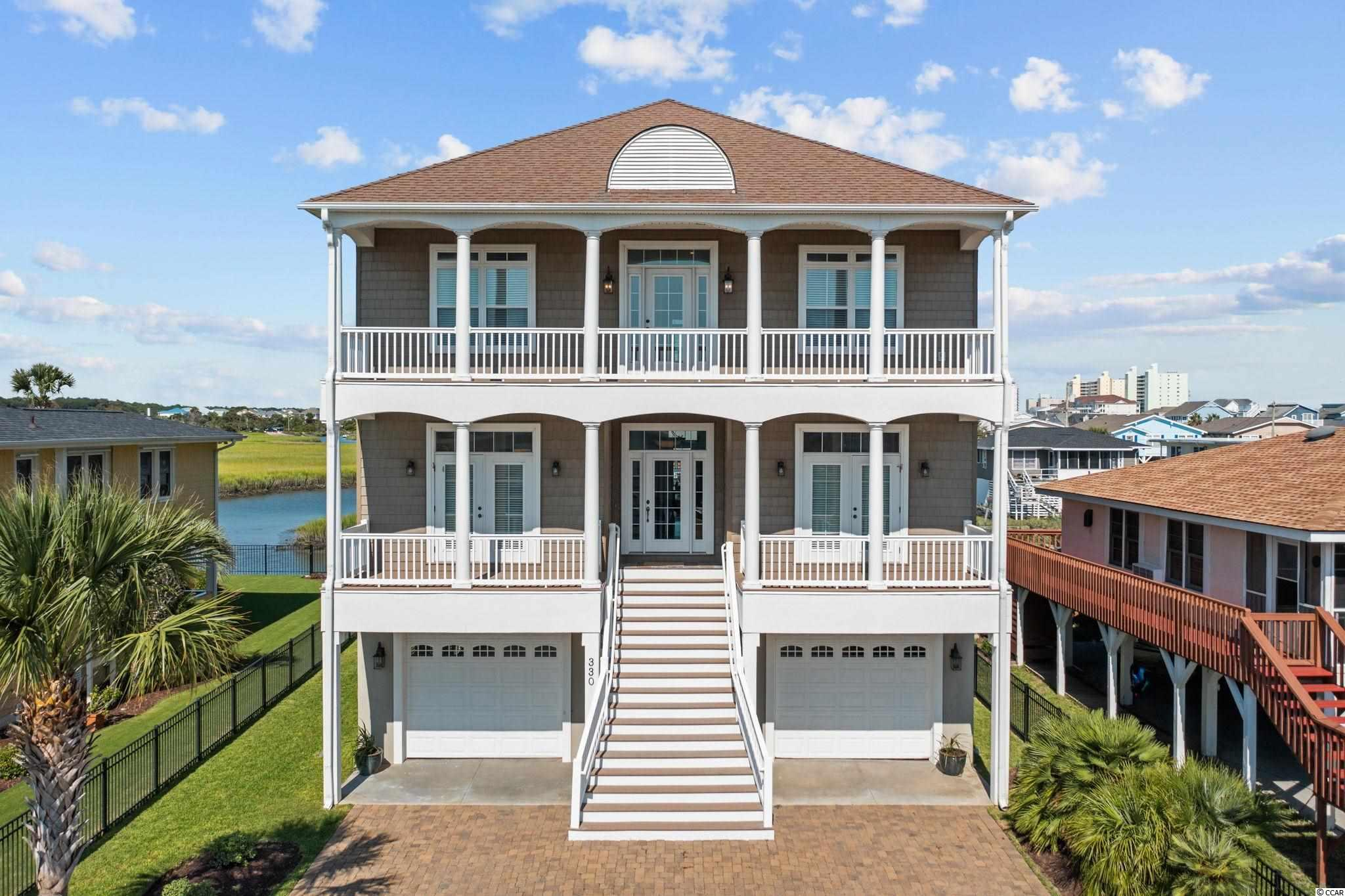 Stunning low country styled beach home located directly on the marsh in Cherry Grove Beach.  This property was custom built in 2008 by the current owners with top of the line detailing and hand selected finishes.  Prime location with outstanding views of the channel, marsh and Tidewater golf course.  The lot location provides quick access into the main channel and ocean navigation within minutes.  Whether a second home or primary residence, everything you could ask for in a beach home has been thought of here.  Classic raised style, the ground floor has two garage bays with one acting as an open air breezeway.  The other bay is fully enclosed with storage rooms between the two.  As you enter the home on the main floor, you immediately notice the level of detailing.  Not only has this home been expertly constructed, the interior furnishings and decor have been hand selected and curated.  Most furniture is from Lexington and Hooker with luxury bedding from Pottery Barn and Serena & Lilly.  The property will convey to new owners with a fully furnished interior minus some exceptions.  Heavy crown molding is found throughout, blonde hickory plank hardwood flooring on the main level and a soothing coastal color palette sets the tone for this exquisite property.  The five bedroom floor plan offers space for everyone and plenty of privacy with a living room on each floor.  The main floor has an owners suite with large attached bath.  A secondary main floor bedroom is across the hall with an en-suite bath.  Both bedrooms have french door access to the full length front balcony.  Accessed from the foyer, the heart of the home is an open kitchen, dining and living space.  The rear of the home is lined with windows with transoms above to maximize the one of a kind marsh views.  The living room is a comfortable size and boasts a coffered ceiling.  Elevator entry can be found in the living room and can be used to access either the ground or top floors.  The kitchen features semi 