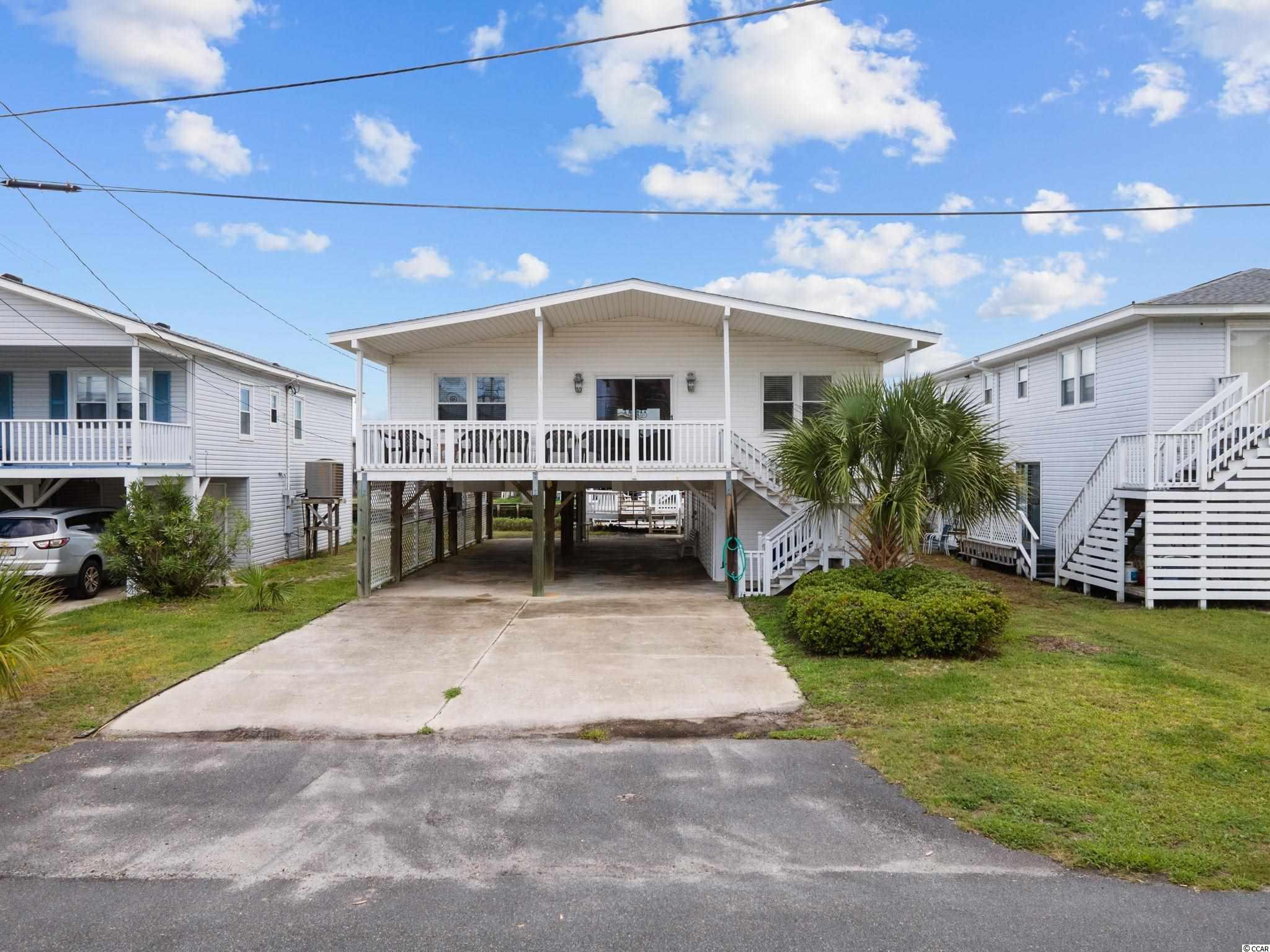 Presenting this vibrant 4 bedroom 2 bath raised beach canal home located in the Cherry Grove section of North Myrtle Beach. This fully furnished bright and cheerful home offers a new roof that was installed in 2021, a new deck installed on 08/18/21, a new HVAC system installed on 08/04/21, new water heater installed on 6/20/20, elegant hardwood & carpet flooring, vaulted ceiling with fan, spacious main living/dining combo floor plan, and a delightful balcony area with breath taking canal views. The fully equipped kitchen includes white on white appliances, smooth flat top range, refrigerator, dishwasher, along with ample cabinet & counters space. Each of the comfortable bedrooms are connected with a with a timeless full Jack & Jill bath. This piece of paradise includes relaxing open air back decks, under house sizable storage areas, and offers an inviting front deck for watching the memorable sunsets. This home affords you easy access to the beach and golfing along with all of the other activities and happenings in North Myrtle Beach & Myrtle Beach including fun eateries, award winning off-Broadway shows, public fishing piers, and intriguing shopping adventures along the GrandStrand. Conveniently located to your everyday needs, including grocery stores, banks, post offices, medical centers, doctors' offices, and pharmacies. Check out our state of the art 3-D Virtual Tour.