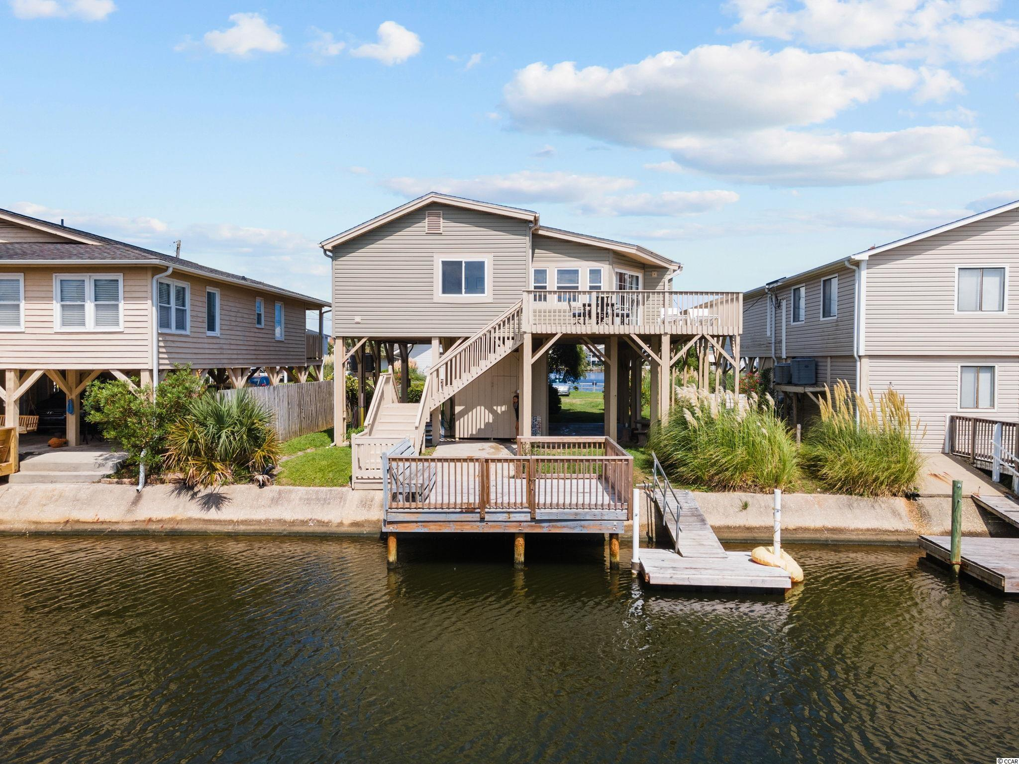 Welcome to Serendipity and your chance to own a little piece of the beach!  Wonderful open and cozy floor plan and outstanding water views.  You could not ask for a better location in Cherry Grove!  Classic raised beach house construction on the lakefront with a fixed deck over the water and floating dock.  This home was built substantially higher than surrounding homes and has virtually no flooding risk.  A concrete bulkhead is in place and provides low maintenance.  As you enter the interior of the home you'll find an open floor plan with a spacious kitchen, dining and living area with vaulted ceiling.  It's a great space for family and friends to gather.  Windows fill the living and kitchen areas providing a 180 degree view of the water.  Luxury vinyl plank has been installed in the living areas for easy maintenance and an upgraded look.   The kitchen has plenty of counter space and a substantial breakfast bar for relaxed dining.   Just off of the kitchen is the owners suite with attached bathroom.  A true bonus is the in home laundry room adjacent to the owners suite.  On the opposite side of the kitchen you'll find two additional bedrooms and a hall bath.  A large wrap around deck has been added to the home to take advantage of it's prime waterfront location.  Easy access from both the owners suite and living room through sliding doors.  The exterior of this home is vinyl for low maintenance and has vinyl replacement windows and newer doors/sliders.  The ground floor has a large storage area and a spacious outdoor shower.  The home is sold fully furnished and is ready for you to enjoy as a vacation home or as a new addition to your investment portfolio.  Easy and convenient access to the oceanfront by foot or golf cart.  It's just a short walk as well to the Cherry Grove Fishing Pier and dining options.  This home is ready for new owners and is the perfect option for you own piece of the beach!  All information is deemed reliable, buyer is responsible for verif