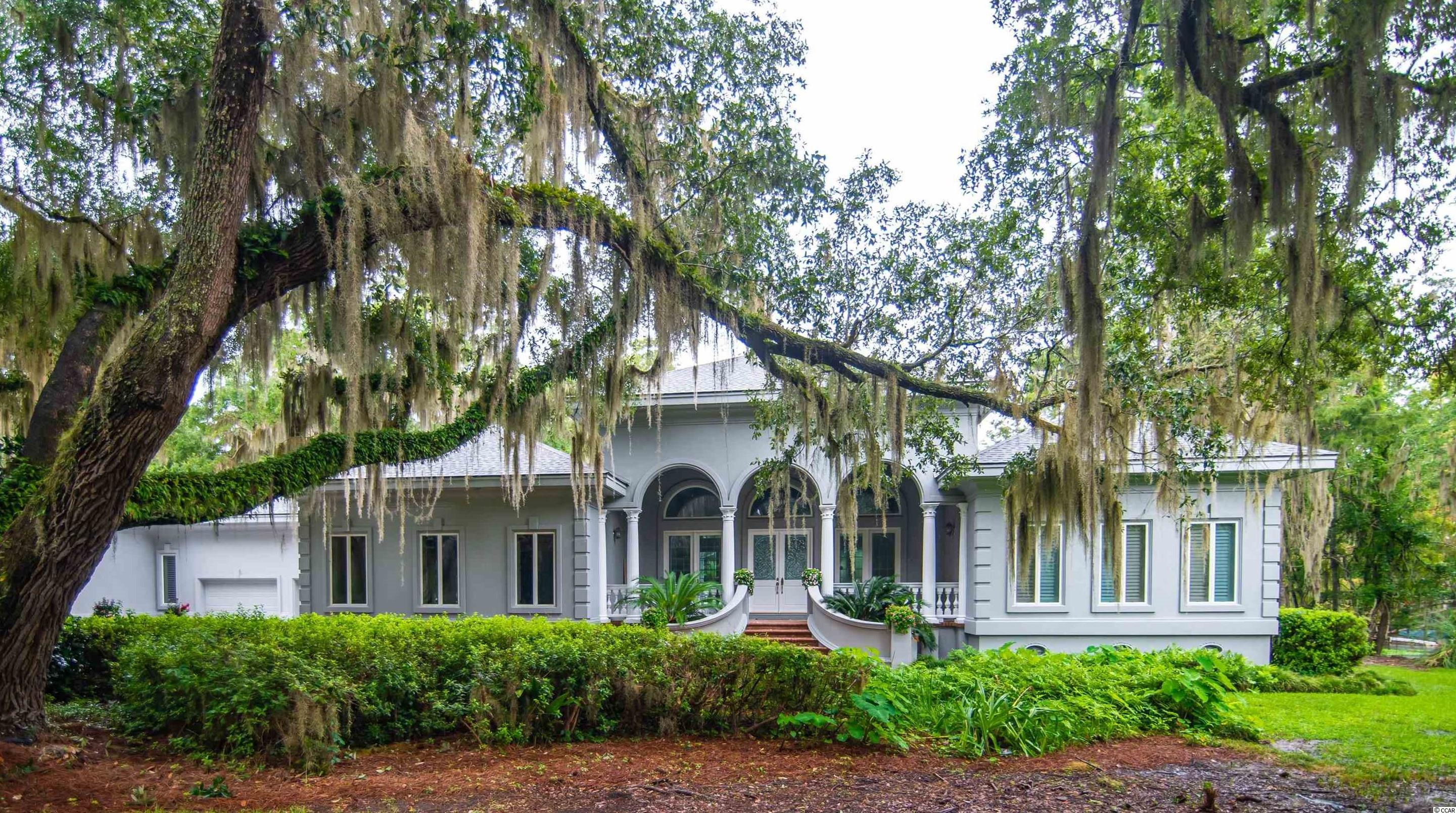 """This splendid, gated home, never on the market before, offers unprecedented privacy of nearly 1.2 acres of your very own """"mini-Brookgreen Gardens."""" This rare property is completely private with protected marshlands along the entire western border. Over 40 majestic laurel, black, and live oaks dripping with moss and surrounded by azaleas, cover the grounds providing unparalleled Lowcountry beauty and cool shade.  This estate offers 180-degree water and marsh views and its own private dock with tidal, Oatland Creek access to the Waccamaw River. THIS is the property that everyone has been waiting for!   This luxury residence, two years in its construction by craftsmen, showcases a palladium-style front porch, loggia great room with Turkish marble floors, a marble fireplace, custom crown molding throughout, an impressive 21-foot formal entrance, cut-crystal chandeliers, original hardwood floors, and a private, custom pool and columned lanai as its centerpiece. The owner's bedroom features his and her bathroom suites, and a pecky cypress-lined, private den which can also function as a separate bedroom if desired. Two other en-suite bedrooms offer privacy in the south side of the house. The current formal dining room can easily be repurposed as a splendid family room with glorious views of the sunset.   Surrounded by this quiet and peaceful, large, natural property, you will only have fleeting glimpses of neighbors across the water. The only sounds are water birds on the marsh and owls in the oaks. This property simply must be seen to appreciate how private it is, even though it's so close to the conveniences of Pawleys Island. Not only will you enjoy the privacy of your own gated property, the full cul-de-sac can be yours with the purchase of the adjacent lot, making the entire end of the street your private piece of heaven.   Enjoy your exclusive community pool, active clubhouse, and the Dan Maples Signature Willbrook Plantation Golf Club, all just a short golf cart rid"""