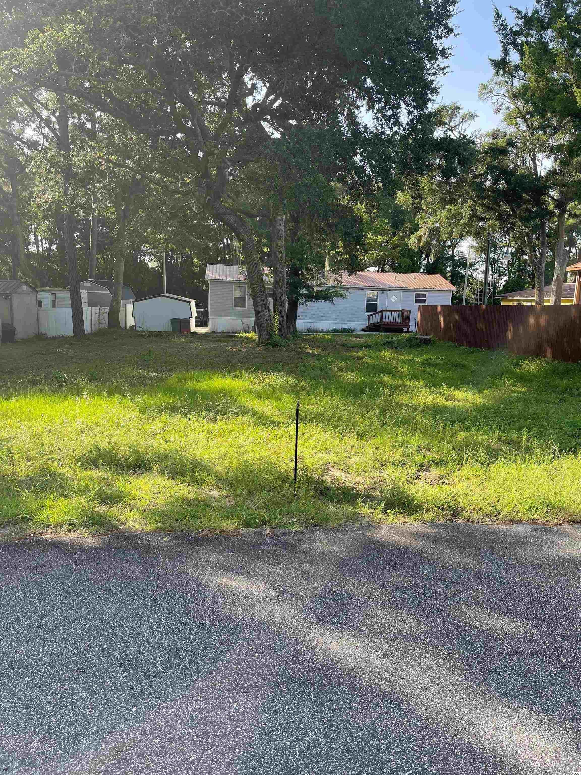 Nice lot in The Grove only a short golf cart ride to the beach, shopping, restaurants and entertainment. You can have mobile homes, modular or stick built with NO HOA's