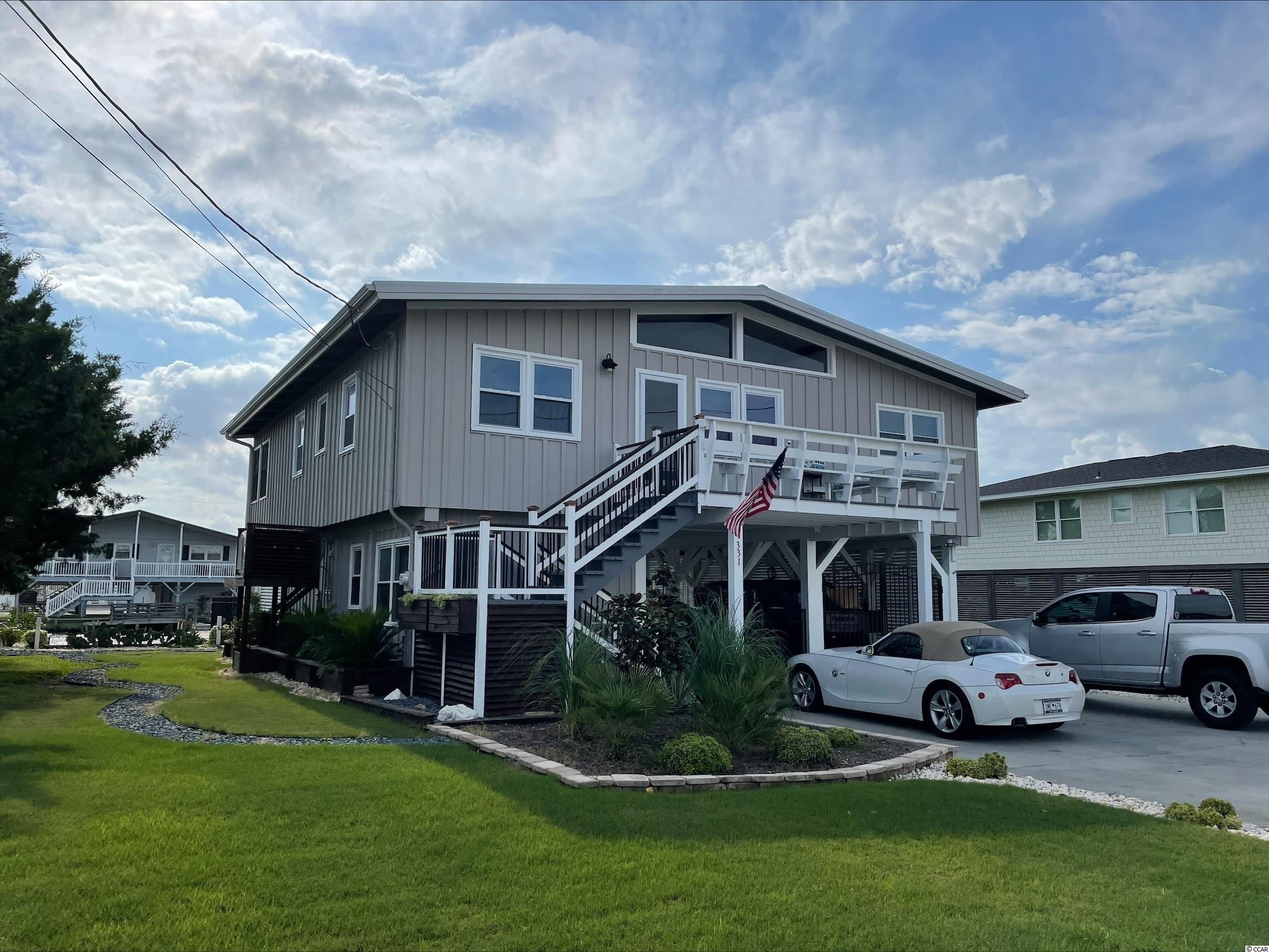 More photos comin soon. This raised beach home located in beautiful Cherry Grove area of NMB is a must see! The home boasts an approximately 9500 square foot lot on the inlet, a private boat dock/slip, metal roof and has 3 bedrooms and 2.5 baths. The home has been updated and will not disappoint! New sprinkler system (1 year old) in the home and irrigation outside the home. Washer and dryer convey the washer is 2 years old. Newer tankless water heater (3 years old). Fenced backyard offers a great space for playtime. Way too many upgrades and options to mention! Schedule your showing today. Don't miss out on your opportunity to own a slice of paradise just blocks from the ocean! Square footage is approximate and not guaranteed. Buyers responsible for verification.