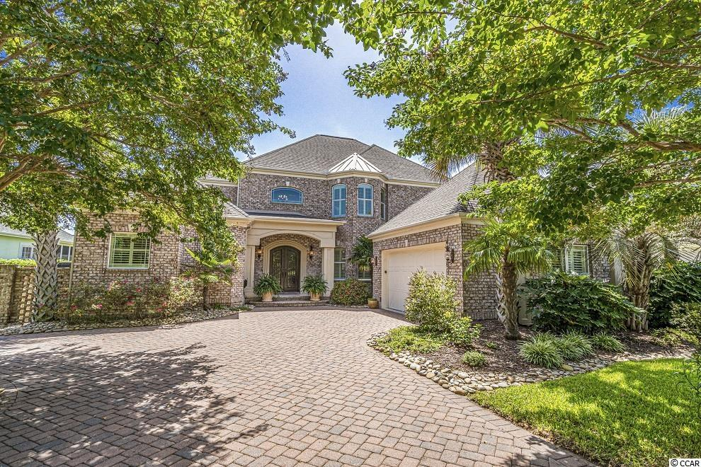 Expert craftsmanship abounds throughout this custom-built, brick home backing up to a lake within walking distance to the beach in the highly sought-after gated community of Seaside Plantation. A paver driveway and steel entry doors welcome you to this exquisite property adorned with arched doorways, bullnose edges and exceptional crown molding among the countless high-end finishes. And this home, which offers water views from nearly every room, will be sold furnished! Magnificent 18-inch ceramic tile flows throughout the entire first floor, which features a spacious master suite with granite counters, an elegant tile shower and a self-cleaning spa. Natural gas lines feed the range in the gourmet kitchen, the fireplace in the great room with soaring ceilings, the Rinnai water heater and the brand new, brick-mounted exterior grill. And you'll be hard pressed to find a better screened porch anywhere along The Grand Strand! Other notable features include: a sophisticated security system with cameras; a commercial grade central vacuum; high impact glass in doors & windows; plantation shutters; motorized chandelier lifts; abundant storage; audio system; garage with room for two vehicles & a golf cart; exterior uplighting; paver patio. This home is literally bursting with upgrades, you must experience it for yourself. The Seaside Plantation community pool and clubhouse are located just a few lots down the street too. Call your agent and schedule a showing today!