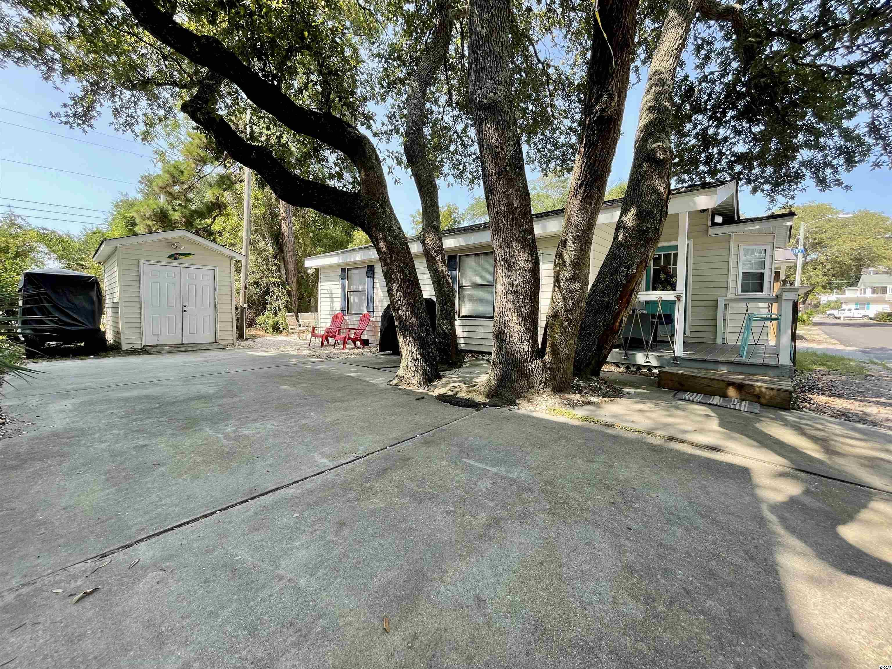 NEW TO MARKET IS A RECENTLY UPDATED 2 BED/2 BATH SWEET BEACH COTTAGE IN OCEAN LAKES JUST STEPS TO THE BEACH ON WIDE SAND DOLLAR DRIVE WITH COVERED PORCH AND PLENTY OF OUTDOOR SPACE! This adorable little beach house is not only in a great location just steps from the blue Atlantic but it also boasts of a great lot with shade from gorgeous, southern live oak trees, a covered porch with Trex decking, lounging and grilling area on the back lawn, outdoor shower, a large paved driveway and a detached garage to store your golf cart and all your beach gear. Entering the home you will love the newly updated kitchen with tile floors, stainless steel appliances and a sweet granite breakfast bar; new LVP flooring in the family room and bedrooms; updated baths with tile flooring; new furnishings and decor with sleeper sofa; flat screen TVs and more.! Home is being sold fully furnished excluding some wall art and the coffee table. New roof in 2020 and 3 Daikin mini-split, ductless HVAC units. Great Investment! Must honor 2021 rentals.   There is NO HOA in Ocean Lakes. Home is located on leased land, which is payed in semiannual installments with half due in January and half in July.   Amenities abound in Ocean Lakes' gated community and include almost a mile of pristine white sand beach, 24 hour security, trash pick-up, free cable TV, indoor/outdoor swimming pools, water park/slides, lazy river, splash zone, 2 full size basketball courts, miniature golf, fire pit, corn hole, shuffle board, horseshoes, ping-pong, Sandy's Down-under skatepark, recreation building, arcade, general store, golf cart rentals, Sandys Meet & Eat restaurant and more!
