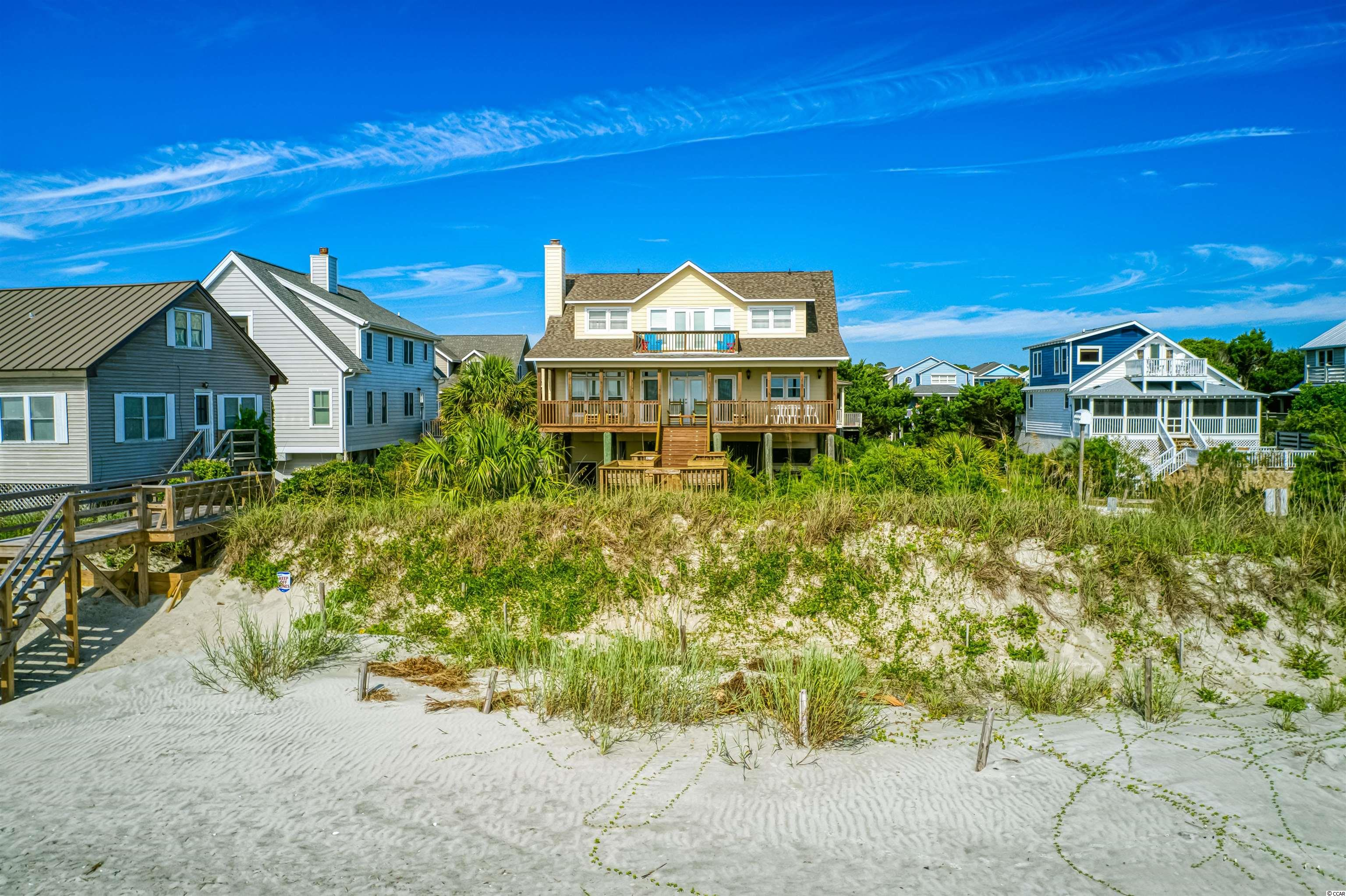 Pawleys at its best! A North end Ocean front one-owner and newer-than-most family retreat. Built after Hugo to new codes, this home has limited rental experience and is located on the great beach at the north of Pawleys protected by high dunes. Enjoy the home's comfortable interior and outstanding ocean views. A large 41-foot-long front porch for big gatherings greets you and leads you into the open front area of the home's living and dining and kitchen spaces.  This area has beautiful knotty pine walls and large pine plank flooring recalling the old times of the Island. The kitchen offers a modern breakfast counter arrangement and views of ocean and includes, smooth top stove, a dishwasher, and plenty of storage.  The master bedroom with full bath and a guest bedroom with full bath are located on this main floor.  Upstairs the view is the best, with a great room with glass doors allowing walkout to beach side balcony. A perfect place to relax or host friends. Fill it with games and activities on rainy days or open to the ocean and enjoy the Atlantic breezes. To north and south of great room are large bedrooms each with full bath. On the rear of house is a long room used as the 5th bedroom under the eaves. The young at heart will pick this room every time.  Home has great storage underneath and plenty of parking. It offers open and enclosed showers with hot and cold water.  A dry entry stairwell leads to the Kitchen area above. In front is the gathering place on the homes private beach front sitting area. The ideal place for morning coffee and evening cocktails while watching the surf activities.  This ocean front home is move in ready, fully furnished, and available for immediate occupancy. Start your Pawleys Legacy in this fine family ocean front address. But hurry!