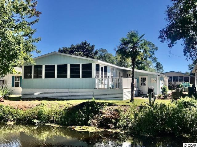 """Very desirable spacious 3 bedroom 2 bath home located in the gated and golf cart community of Oceanside Village. Amenities include, outdoor/indoor pools, tennis courts, library, fitness center and PRIVATE BEACH PARKING AND ACCESS and much more.....  This home features: updated kitchen cabinetry, stainless steel appliances and a beautiful tiled back splash. The focal point is the navy blue bead board ceiling which is classic and timeless with the updated overhead lighting over the kitchen island.    All matching laminate flooring throughout the entire home.  All furniture and decor will convey with the sale of this home.  The 24 x 10 approx. Carolina room offers vinyl windows with a storm door leading out to deck overlooking the canal where our beautiful birds and swans inhibit our lakes. French doors send you into another """"Carolina room"""" with lots of windows for light, side door entry to deck and a futon for more sleeping areas and a corner desk for the at home workers.  Space is not an issue in this home!  Master bedroom has its own master bath with double vanity and linen closet.   This home is manicured on the inside as well as the outside : Outdoor shower, shed, carport and a nice small backyard with a grilling area.  This is a MUST SEE !!!!!   BANK FINANCING AVAILABLE!"""