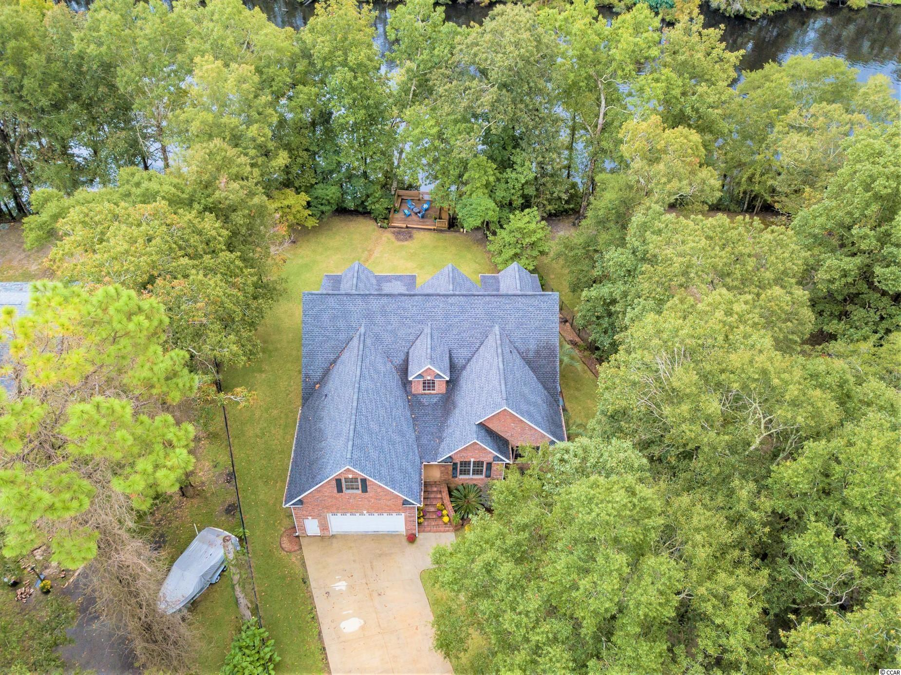 Nothing could be finer than to be in Carolina on the R-I-V-E-R! Introducing 412 Apache Road located on Black River in historic Georgetown, South Carolina!  Beautiful custom built all brick home sitting on .80 acre lot. With five bedrooms and a huge bonus, there is plenty of space for everyone to enjoy.  As soon as you enter the foyer your eyes will be drawn straight to the back French doors and out onto the water. Throughout the home you will be impressed by the gorgeous oak floors, stained trim/moldings, custom blinds, solid wood doors and efficient tankless water heater. The main living level showcases a large great room with vaulted ceilings, gas fireplace with built-in bookshelves, open kitchen/dining area with large breakfast bar, granite countertops, pendant lighting, custom cherry cabinets, soft close drawers, and corner pantry. Enjoy your peaceful morning coffee on the screened porch off the kitchen or the open porch facing the back yard.  The large owner's suite is also on the first floor and features tray ceilings, screened porch facing the water, his and hers closets, bathroom suite with shower, jetted tub and separate vanities.  A private study, laundry room and two more bedrooms with a shared bath are also on the main level. Upstairs there is a spacious bonus room, walk-in attic, plus two large bedrooms each with vaulted ceilings, dormer windows with storage bench, and each with multiple closets.  There is absolutely no wasted space in this home, really a functional floor plan. Now let's talk about the exterior!  Giant front yard, overflow parking, two car garage, black aluminum fencing around the perimeter of property, and new roof. In the back yard it's all about the view from the top deck with bench seats overlooking the water, another lower deck and stairs leading to the floating dock and river.  Fish, grill, relax, and not in that order! Apache is also a fun boat ride to historic downtown Georgetown waterfront Harbour Walk where you will find amazi
