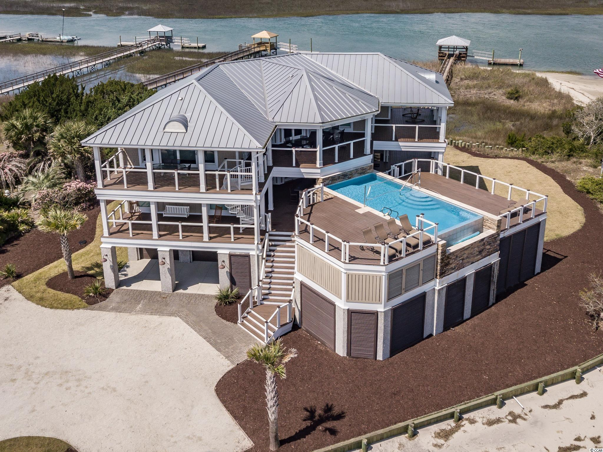 Decked Out, crowns the most northern gated tip of Pawleys Island, perfectly harmonizing with the surroundings while providing panoramic views of the Atlantic Ocean, Midway Inlet, Pawleys & Litchfield beach, and the lush Lowcountry marshlands.  A water lovers paradise, the oceanside elevated saltwater infinity pool and refreshing breezes beckon one to stop and relax in the moment. This exquisite and impeccably maintained residence, built in 2015, offers the finest in beach front living. It's 4,000 square feet of covered decks provide stunning and unique views of this magical location.  A spacious outside bar with 60 inch large screen TV and 2 pool decks is a focal point for entertainment. The heated infinity pool with stacked stone waterfall is just steps from the beach while the private covered and floating dock provides easy entry to Pawleys Creek. Inside, the reverse, open floor plan includes rustic hickory floors, a gourmet kitchen with stainless steel appliances, a wine fridge, ice maker and quartz countertops. The kitchen and dining area blends comfortably with the family room while the large Andersen hurricane impact windows with oversized sliders provide fabulous natural light and wonderful views throughout the home.  This fully furnished, six-bedroom home sleeps 16. Additional features include surround sound wired inside and out, gas log fireplace, Trex decking, pool floor deck misters for added comfort, stainless steel cable railings, metal roof and full service elevator. The ground floor garage is spacious and allows multi use capability for vehicles, boats, golf carts and even a recreational game area. Boasting more than 2-acres of beach and creekfront access, this stunning location with built in seawall offers deep water entry for boating, fishing, crabbing, kayaking paddle boarding, birdwatching, stargazing and of course unparalleled sunrises and sunsets. House also comes with built in rental revenue for 2022. Previous rental history available upon requ