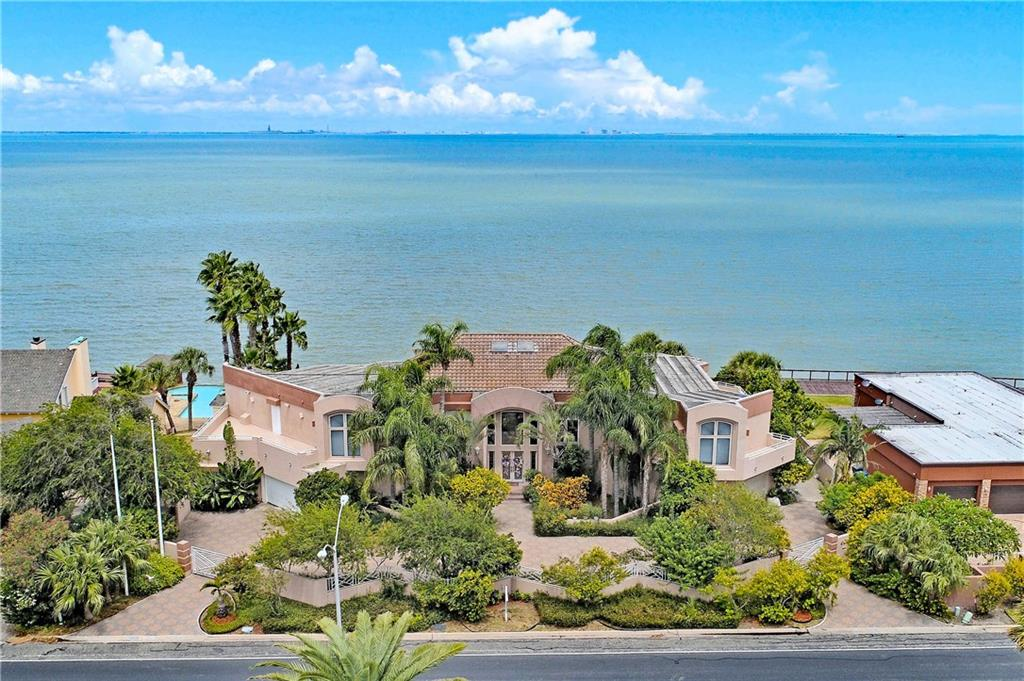 Fabulous waterfront estate located on prestigious Ocean Drive boasts stunning views of CC Bay & skyline thru out the home! Grand foyer, great room with two story high ceilings, wall of windows & solar room with panoramic view welcomes you to this unique property. Gorgeous wood bar with long curved granite counter is a focal point. Other features include formal dining, three way fireplace, media room, two staircases, downstairs bedroom, bath off kitchen. Gourmet island kitchen, granite counters, custom cabinetry, subzero & spacious breakfast area. Master (down) with loft area(exercise, office) with elevator access. Second floor game room, two wet bars, wood dance area/den & balcony overlooking great room. Indoor heated pool with hot tub. Exterior features beautiful pool, full bath, patios, enormous wood decks(approximately 15 foot piers) for sunning, birdwatching & sunrises over the bay. Seawall, retaining wall, electric storm shutters. House foundation has approximately 34 foot piers.