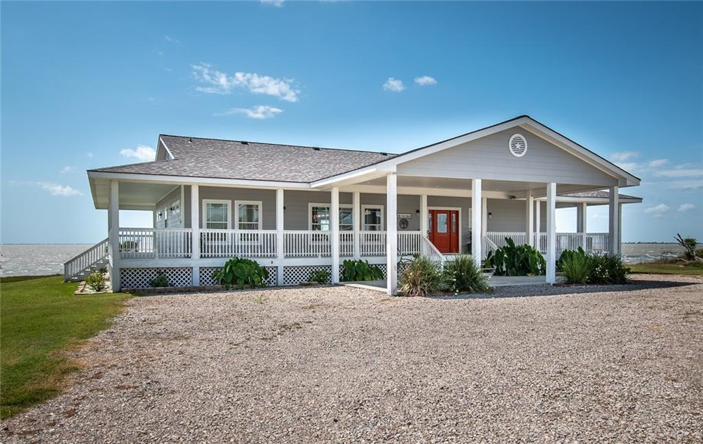 PRICE REDUCTION!  Fabulous, Breathtaking, Stunning are just a few of your thoughts as you sit on any of the four covered porches of this beautiful 3 bedroom 2.5 bath home on Copano Bay! 375 ft pier with 8x16 T-head and 8x 10 fish cleaning kick out  to maximize your water fun in back and a 1400 sq. ft. guesthouse/workshop and garage with expansive lawn in front. Generous open floor plan, and split bedrooms and a game room with bar to add to the fun. The living area boasts tons of storage and custom built-in,s and the kitchen is a cooks dream with a huge quartz island that easily seats six! Perfect for Air B n B rental as well as private home. With an eye for detail and every upgrade and luxury you would expect in CoastalWaterfront Living, this home has been overbuilt to withstand the strongest winds, boasting a new roof under warranty.  This is truly the pot of gold at the end of the rainbow. Take 3rd st. Right on Center and then follow around the Bend back to First St. home on right.