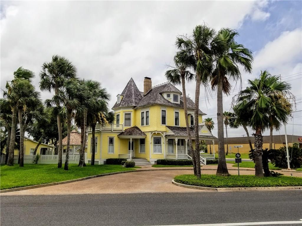 """The Hoopes House, a Rockport icon.  This beautiful yellow house welcomes residents and visitors to the dowtown heritage district.  Completely renovated and restored in the late 1990's and meticulously maintained since that time.  It is listed in both the National and the Texas Register of Historical Places under the name """"Hoopes-Smith House."""" This Queen Anne style home is a three-story main house, built in 1890 with 3244 square feet of living space, 4 bedrooms and 4.5 baths.  The second structure is a 1547 square foot pool house with 3 guest rooms with baths, built in 1995.  The last structure is an in-laws/caretakers apartment with 846 square feet, one bedroom with kitchen above the laundry/utility area with a half bath (506 square feet) also constructed in 1995.  The grounds are lushly landscaped and completed with a pool, hot tub and gazebo.  There is a two-car garage and separate 2 car/boat covered parkling under apartment, plus additional paved guest parking.  ***"""