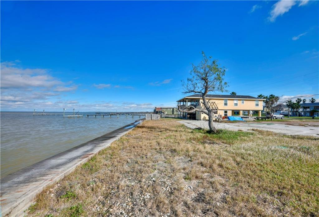 Fabulous panoramic views can be had from every room of the house that you build! AN OVERSIZED Copano Bayfront lot, buklheaded and ready to build upon, your waterfront home can have views of the Bay, The Channel and Salt Lake! The Copano Bay sunsets are what writers write about and artists paint. Solid blues fade into pinks that melt into oranges, and you can enjoy every second of the fading glory as it dips behind the horizon. The lot already boasts an aerobic system, a bulkhead running the length of the waterline, a concrete driveway from the street to the previous home site and three car garage. The home used to boast a pool, since the storm all debris was removed from the pool and the cavity filled with clean sand. Just a short distance to a boat ramp and world class bay fishing and Birding, this location is truly remarkable. Prior to the storm this location was the setting of some wonderful family memories. Let 304 Copano Ridge Road be the back drop to your wonderful memories.