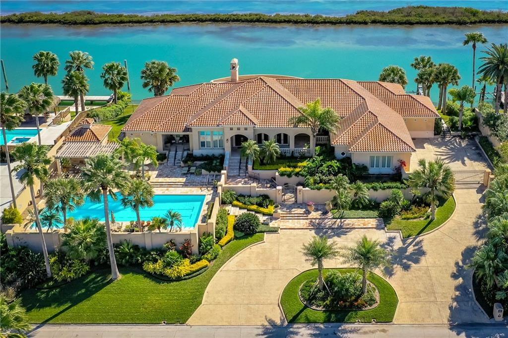 This waterfront Mediterranean-style residence is situated high atop the Pelican Cove levee with direct access to the intracoastal waterway. This stunning, gated waterfront estate boasts 3 bedrooms, 3 1/2 baths, a workout room which could be converted into a 4th bedroom, 4000 sq ft of living space, limestone columns & floors, quarter sawn oak floors & cabinets, and a 3 car garage. Outdoor spaces feature an oversize lap pool and 195' of waterfront with a fishing dock area and 2 boat lifts. Water depth is 12'+, which could accommodate an 90'+ yacht. A vast veranda spans the entire back of the home and offers spectacular sunrise views. This is a bird-lover and fisherman's paradise!