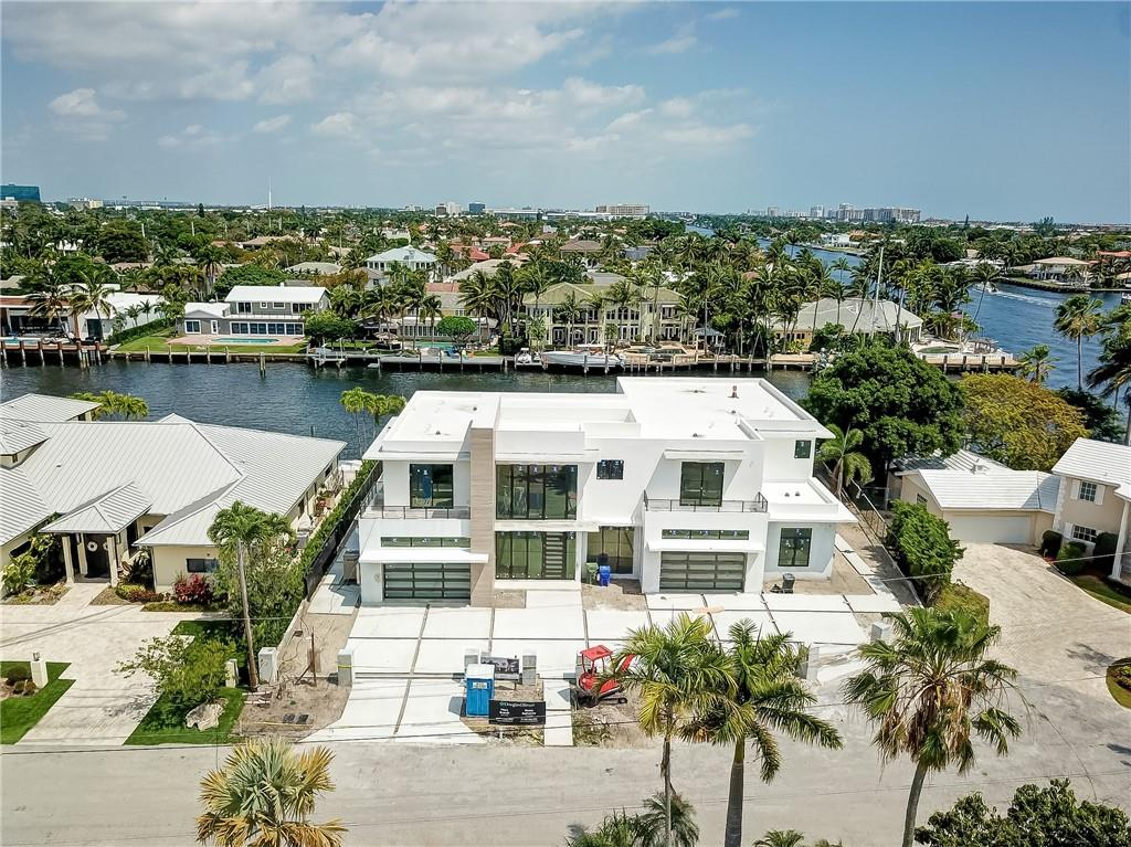 This magnificent new construction home is situated one lot from the intracoastal waterway and on the widest canal in Coral Ridge Estates, with 125 feet of water frontage. Built with no expense spared, this masterpiece features: 2 master suites, two 2 car garages, an open/flow through floor plan downstairs and water views from almost everywhere in the house. Located across the street from Coral Ridge Country Club and built of the highest quality, this property will blow you away.