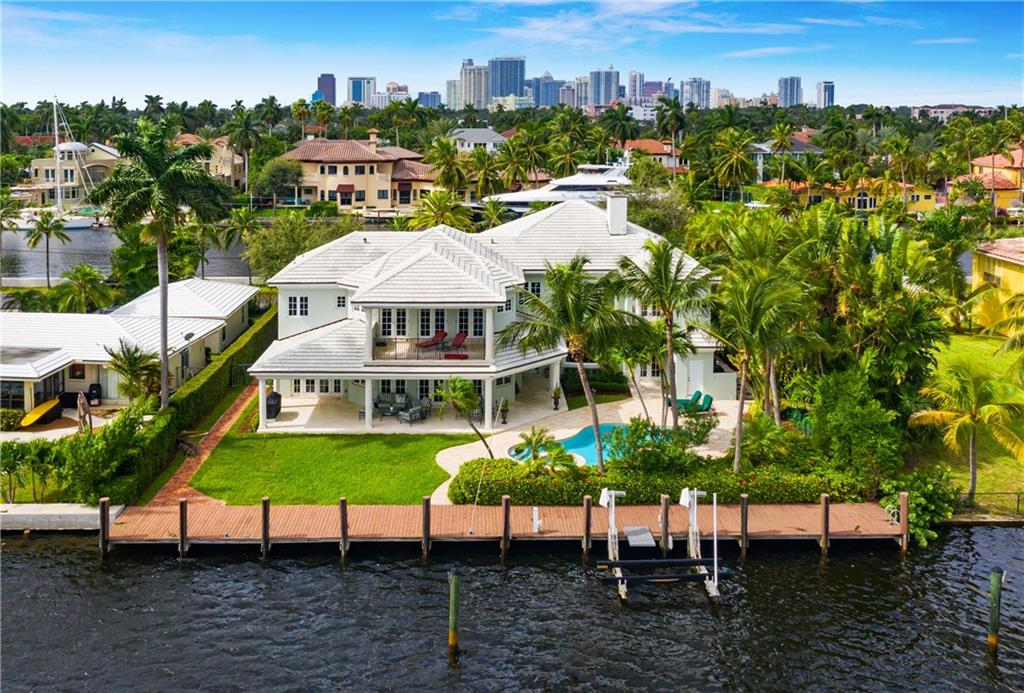 Not to be overlooked if you are seeking wide open views under $6M. This elegant Georgian-inspired water wonderland has additional privacy with no residence across the isle and 100ft of waterfront views! Unequalled almost every room in this home has a water view Enjoy the highly unique deepwater ocean access PLUS wide open lake views. The opportunities for water activities are endless! Great protected dockage with electric, water and 15,000lb boat lift, kayak, paddleboard etc. This timeless traditional two-story, 6 bedrooms, 7 1/2 bath home shows beautifully. Over 5,000SF of indoor living space, expansive outdoor living with pool, hot tub and covered loggia. Great floorplan includes a first level home office, VIP guest suite, separate in-law/captains/nanny quarters. Must see to appreciate!