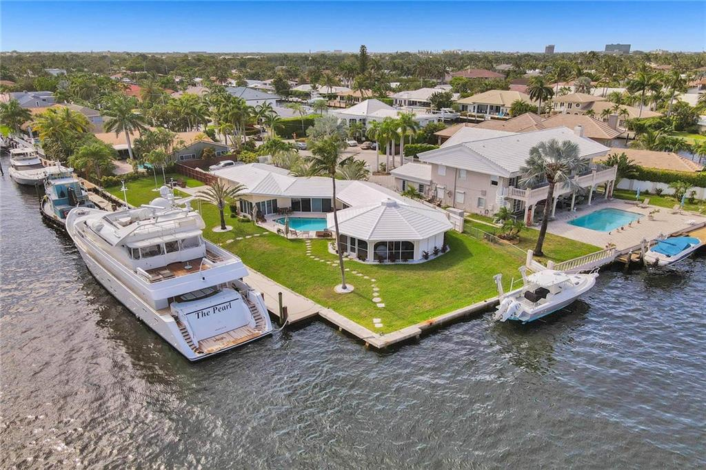 Coral Ridge Country Club, point lot with nearly 200' of dock in a no wake zone. Build your dream home or dock your yacht and put your crew in the house. 3/2 pool home with 2 car garage. Intracoastal views all day long!