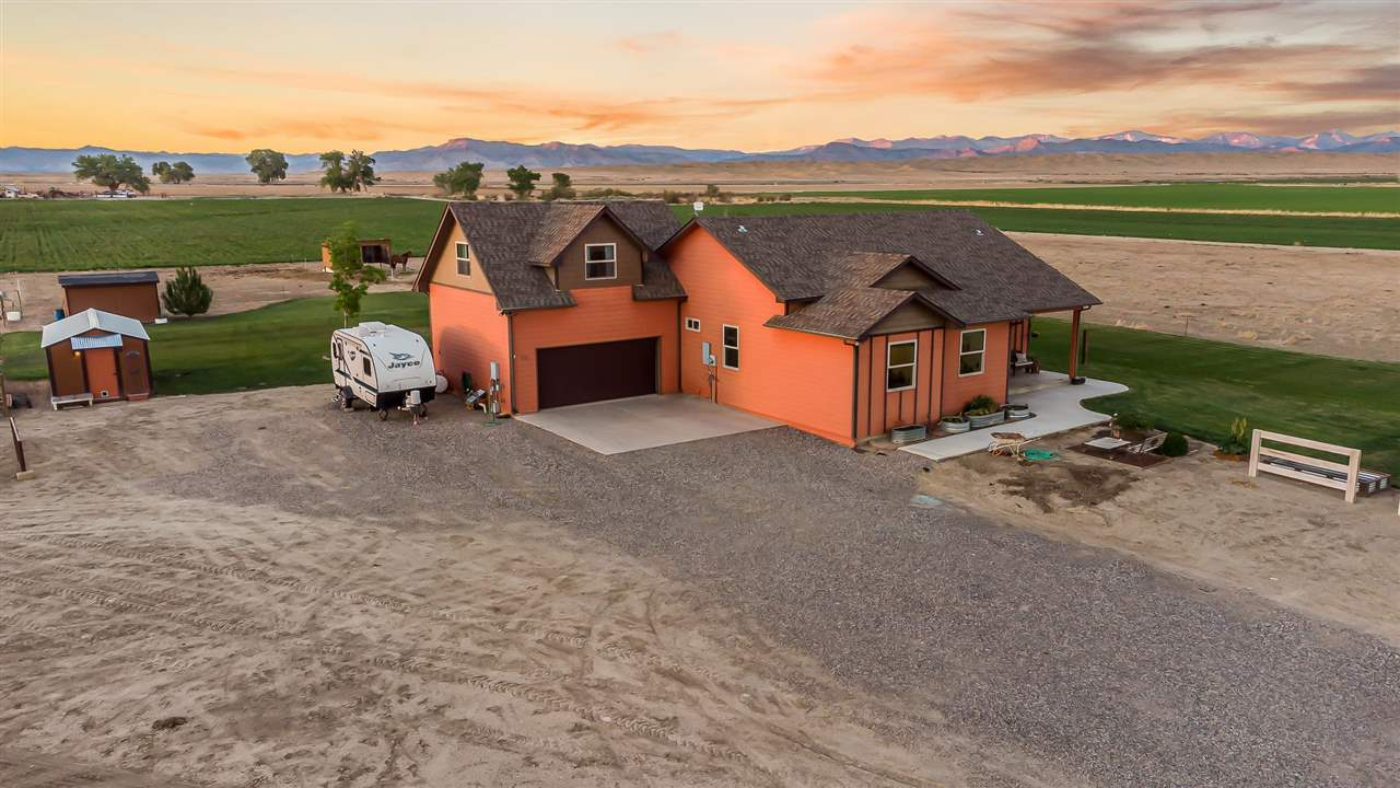 """Country living at its finest combines with 360 degree panoramic views on this 3.62 irrigated Loma property adorned with a custom-built farmhouse. Geothermal heating and cooling along with a wood burning stove add coziness and convenience to this beautiful home. From the front entrance, two sets of French doors opening to the back yard and pasture bring in natural light plus provide stunning views of the surrounding Colorado mountains. The kitchen is the heart of this country home where you'll love the counter seating, copper and rivet countertops, open shelving, stainless appliances, and gorgeous farm sink. 10"""" pine plank flooring expands throughout the main living space adding additional warmth and rustic charm. Upstairs, an extensive bonus room with reading nook and full bathroom offers a multitude of options! Sheds, room for all your toys, and space to breathe!!!"""