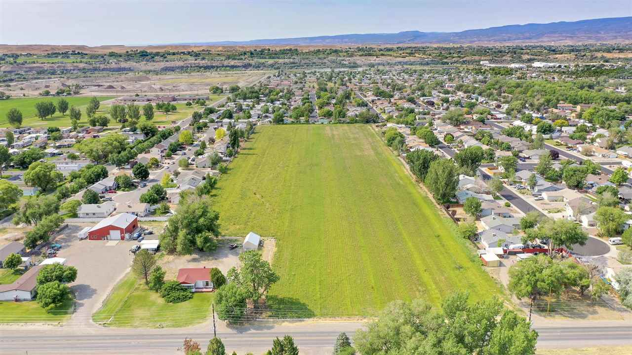 12 acres of development opportunity off of E Road. Current zoning is RMF-8 (5-8 homes per acre). Perfect for single family, multi-family development or buy the property and build your dream home. The current 2 bedroom, 1 bath home has hardwood floors, a wood burning fireplace and is ready for your TLC. Approx. 10.5 acres are in hay production with ample shares of Grand Valley Irrigation water. Buyer to do due diligence.