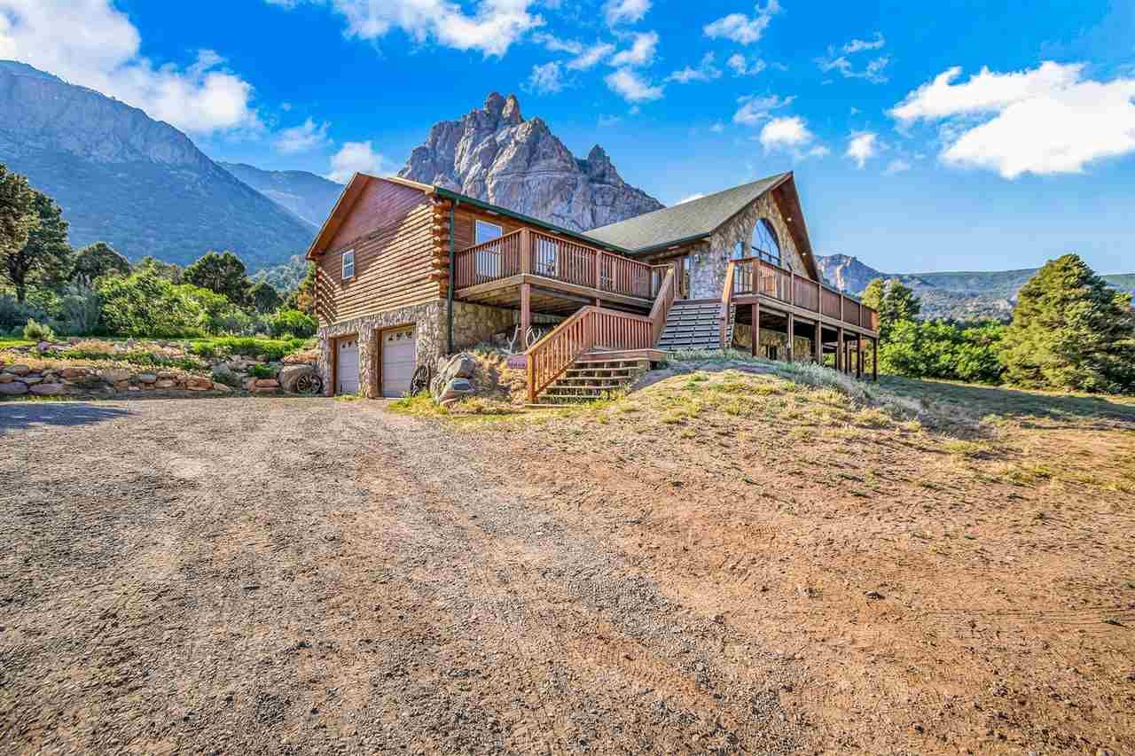 Have you ever dreamt of owning a mountain retreat? This Gorgeous custom log home sits in one of the most beautiful locations in Colorado. Based in the Unaweep Canyon with views of the historic Driggs Mansion and Thimble Rock out the front window. Enjoy 360° views with the wrap around deck. The property backs to BLM with trophy Unit 40. The property across the road is in conservation. With just over 4,900 square feet, 5 bedrooms, 3 baths, a bar, game room, theater room, open concept living room and kitchen with vaulted ceilings, 4 car garage, arena with roping shoot and calf pins, tac shed and a pole barn. Arch windows, radiant in floor heat, solid D logs. 22 acres of wooded area with a natural spring/pond. Call to schedule your showing.