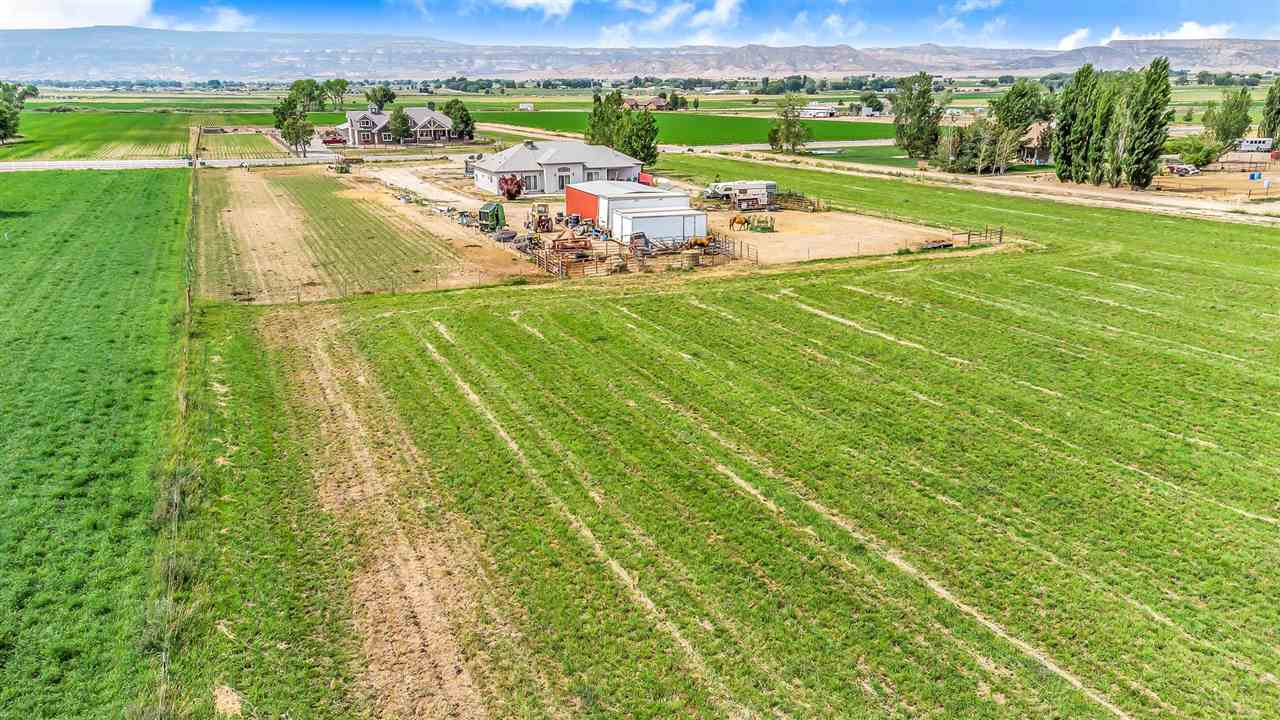 Country living at its finest! Custom 3 bed, 2 bath home on 9 irrigated acres. Bring your horses, 4-H animals and more! Located in beautiful Loma, this property provides quick access to the interstate, Fruita and Douglas Pass while allowing for plenty of open space. Surrounded by green pastures with incredible 360° views of the Bookcliffs, Mesa and Colorado National Monument. Including a 24' x 36' shop, heated garage with 220v, gated irrigation pipe with socks, plumbing and electric to back patio and fully fenced. The evaporative air conditioning is vented to the Primary Bedroom, hallway, Living and Dining Rooms. There's plenty of room for a regulation size arena at the back of the property. Including fruit trees; 2 cherry, 2 apple, and a peachcot! Bring your animals, toys and dreams and live the country life!