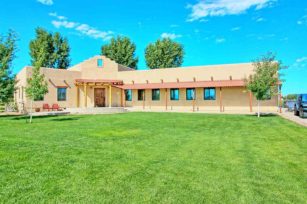 The one you have been waiting for! This beautiful 3 bedroom, 3 bath, 2854 sq ft Spanish style home sitting on 4.53 irrigated acres has everything you have been looking for, inside and out, top to bottom. From the gorgeous pine flooring, to the 9' ceilings, extra-large laundry room, and a beautiful office. Mature landscaping with fantastic views and plenty of room for livestock with corrals already included. This property also includes a 40 x 60 heated, insulated shop with room for your RV, boat, multiple vehicles or other toys along with plenty of additional storage! Inside the shop is a finished studio with a 3/4 bath & kitchen plus washer and dryer. Far too much to share here, come see for yourself what gives this home great value!