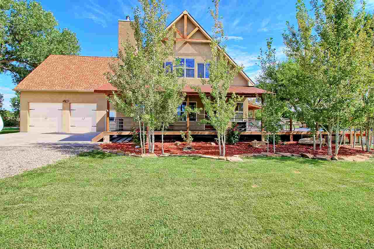 Quietly nestled at the base of Mt. Garfield and the Grand Mesa on over 4 acres at the end of a private drive this one of a kind 2 story, 3 bedroom, 3 bath, 3467 sq. ft home with a bonus room used as a 4th bedroom with a 2 car garage is something to see! Immediately you'll notice the quality, craftsmanship and pride of ownership inside and out. Oak hardwood floors, granite counter tops, water filtration and softeners, beautiful soft close cabinetry, soapstone wood stove nestled in a custom designed arch with original barn wood beam mantle and so much more. Outside you'll enjoy a completely fenced property with mature landscaping, 2x4 wire fence and automatic gate, easy to maintain solid sided pool meeting up with the wrap around deck perfect for family get togethers! Come see for yourself everything this gorgeous home has to offer!