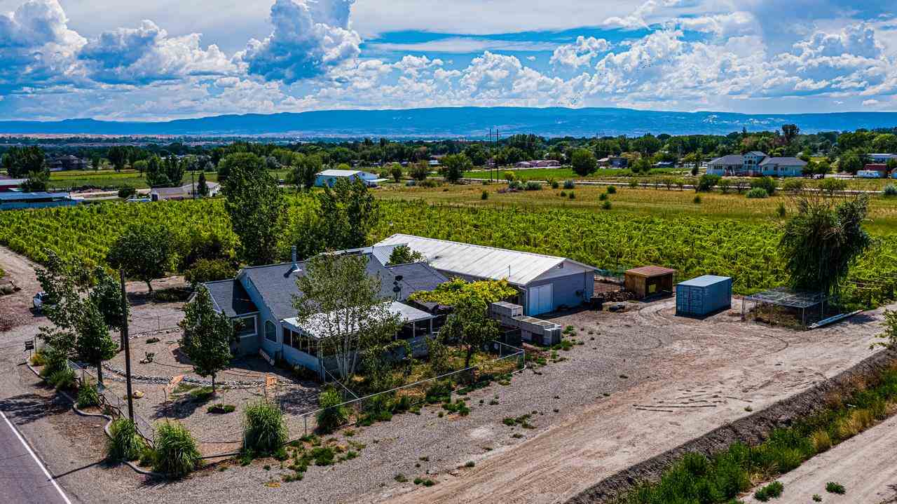 This beautiful, 5 acre organic vineyard includes 38 rows of  Sangiovese and Golden Muscat Grapes. The vineyard is an income producing vineyard and 100% of the crops are sold every year with approx. 80% sold to one long term buyer. These grapes have also won numerous wine awards for their vintner. The property comes with all the equipment necessary for a turn-key business operation and  comfortable living, including 2 heated horse stalls, hay storage, butcher room with all equipment, cold/dry storage, workshop, hot tub hookup, heated screened porch, Swedish sauna, and an owned, operational, PV & Thermal solar system. Water availability is not a worry for this unique property, it is the first gate off of the Government High Line Canal. Enough space for additional equipment, tasting room and more, plus this area currently does not have any restrictions for Air BnB.