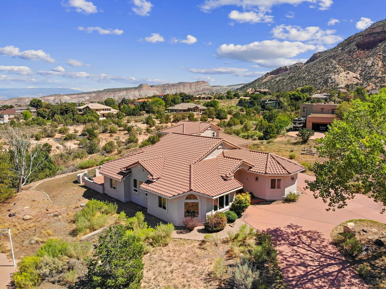 Architectural & natural beauty merge in this wonderful Western Colorado home. Nestled in at the base of the Colorado National Monument, the spacious layout offers 360 degree views of not only the red rocks & desert canyons just steps away, but also across the valley to the Bookcliffs & Grand Mesa. Inside you'll find peace, quiet & privacy as the floor plan allows for clearly defined places that flow gracefully into one another. With two generously sized living spaces, a formal dining room & open kitchen, entertaining is easy. The office offers both storage & a built-in safe. The master is a true retreat set away from the main living space. Upstairs is a mother-in-law suite with a balcony all its own. The oversized 3-car garage is impressive & the back patio with putting green offers the best valley views. Don't miss out on this Grand Junction wonder!