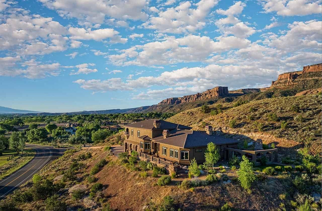 Absolutely Remarkable Private Sky-View Estate with Unforgettable Starlight & Sunset Views; Overlooking the Entire Grand Valley & Seated At the Base of the Colorado National Monument & within walking distance to World Class Hiking, Biking & the Great Outdoors! This Unique & Innovative Spanish Colonial Designer Home Built in 2008 Features: 4360 Sq. Ft, 5 bedrooms, 4 baths, and is seated on its own Mountain with 5.18 Acres & is The Only of It's Kind! The lower area of property also serves as additional building site for casita and/or mother in law! Enjoy Flawless Composition & Masterful Design including Stucco & Rock Exterior, Impenetrable Tile Roof, Gorgeous Veranda W/ Decorative Tile, Stucco & Metal Railing, Elongated Driveway, Beautiful Outdoor Patio w/ Cozy Stone Fireplace & Arched 3 Car Garage w/ Large Bonus Storage Room. Enter through Grand Stone Pillars into your own Private Palace with World Class Interior Finishes Decorated by one of Aspens interior designers w/ unique lighting fixtures from all around the world! The Centralized Kitchen features large granite island & countertops, Viking Stainless Steel Appliances, & Beautiful Hardwood Cabinetry. Enjoy lovely formal dining room w/ gas fireplace, ceiling high built in shelving & sky vaulted ceilings. The first level features relaxing sitting room beside the open concept kitchen, spacious & open family room & absolutely immaculate master suite w/ large walk-in closet, jetted tub, dual vanities & artistic & private tiled shower w/ instant hot water & dual sided gas fireplace. Enjoy additional large bedroom & secondary master suite with large private walk in closet & additional private bath. The upper level features 3 spacious bedrooms, additional bathroom with decorative tile surround & gorgeous balcony with private sauna & more VIEWS! This home is currently a private residence & VRBO, which typically rents for just under $1000 per night! The Grand Valley is home to wonderful art & culture, fine dining, excellent