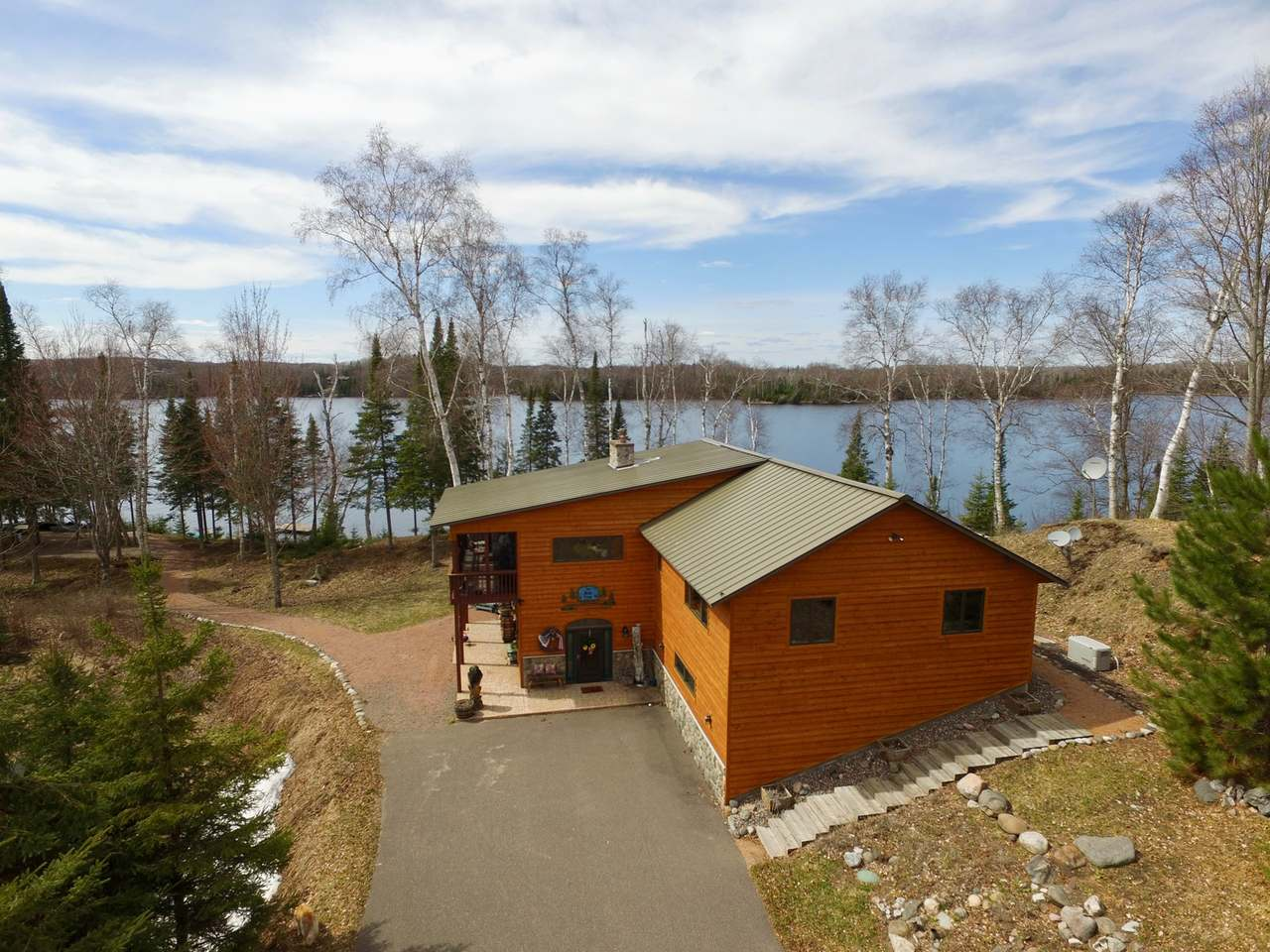 """Spectacular estate located on Twin Island Lake of the Frontier Lakes Preserve. Here you'll find a 4 BR, 3 BA, 3500 sq ft main home and 1300 sq ft guest home all surrounded by towering pines and privacy. The main home offers a spacious kitchen/living area with floor to ceiling lake views, multiple living areas, indoor sauna, and a FP on each floor. This property features 3.85 +/- acres and 303 ft of western facing water frtg , paved fire pit, and lots of outdoor entertaining space. The guest home has 2 separate units each with it's own kitchen, full BA, and lakeside deck. In add, the LL guest home has a gas FP and three built-in bunks to maximize space. The 47 x 29 pole building w/ concrete floor makes a great final addition to the property for storing all your toys. Located just 9 miles from downtown Boulder Junction with lots of shopping, bars, and restaurants. This is the perfect getaway for hosting family & friends for their true """"Up North"""" experience! *Seller Financing Available*"""
