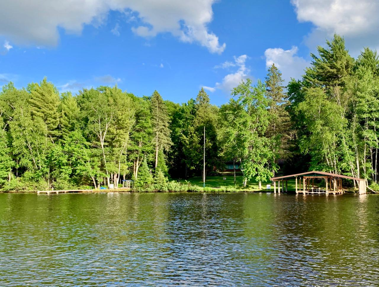 Luxurious log home on the Eagle River Chain. The log home sits on 9.83 very private acres. It also has over 249' of level sandy frontage on Voyager Lake. The home offers 5 bedrooms and 4 baths and over 3200 sq. ft. The home is very Northwoods and is done from floor to ceiling in gorgeous native woods. The highlight of the living room is a stunning curved stone fireplace! The home has two spacious living areas. The one level ranch offers a level lot and single level living. The parcel offers an attached garage and a huge 48' x 40' heated detached garage that also offers additional storage in the upper level. Other features include two furnaces, central air conditioning, backup generator, two pier systems (one with a 3-slip boat shelter with lift), in-ground irrigation system, a long private paved drive and exquisite landscaping.
