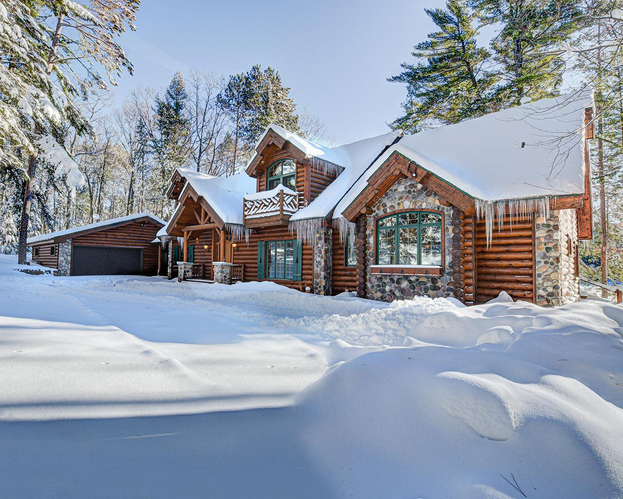 STUNNING log-sided beauty perched on 295' of level sand frontage on the incomparable 3-Lakes/Eagle River Chain of 28 lakes! Tucked in the woods, this majestic home offers loads of Northwoods flair & appeal! Gourmet kitchen w/Viking, Sub Zero & Bosch appliances, granite tops, dbl-sided stone FP, log-beamed wood ceilings, hand carved banister & mantle, lakeside master suite w/his n her vanity & shower heads, & stylish claw tub. The loft has incredible lake views & there are high-end finishes everywhere the eye can see! Finished LL w/a spacious laundry room & custom sauna. There's surround sound, a security system & the covered front porch is in close proximity to the water. Landscaped grounds w/an irrigation system & a beautiful winding blacktop drive. The garage is insulated & has a workshop w/wood heat. At water's edge is a dry boathouse w/electric rail system & a permanent pier system w/covered boatlift. This is a special property waiting for its next special owners, will it be you?