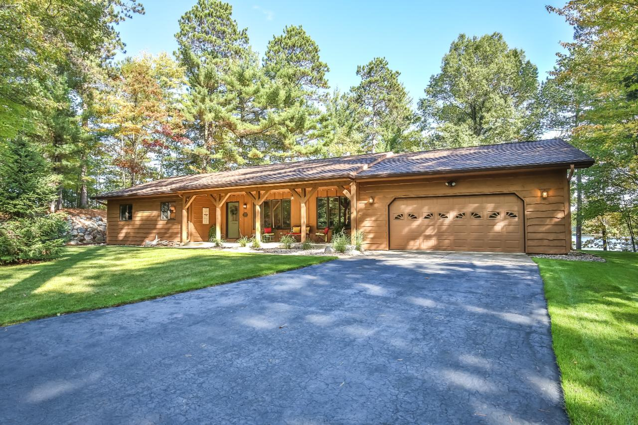 Perched on a point between Boom and Bass Lakes on the Rhinelander Chain is this completely remodeled 3 bedroom, 2 bath home with amazing water and woods views featuring high end finishing from solid maple doors to Amish-made solid cherry cabinets and soapstone counters throughout. The open concept living area offers a large fieldstone fire place with gas insert, basswood vaulted ceilings and maple floors. The custom kitchen is set up to entertain. Large bedrooms, a master suite and both bathrooms with in-floor heat makes this home a great year-round home. Plenty of garage space with a 2+ car attached garage, 2 car detached garage and full unfinished basement. This lot offers a fantastic setting with a large, level lakeside yard and plenty of elbow room from your neighbors with over 220ft of meandering sand frontage. This home offers all these amenities at an exceptional value. --