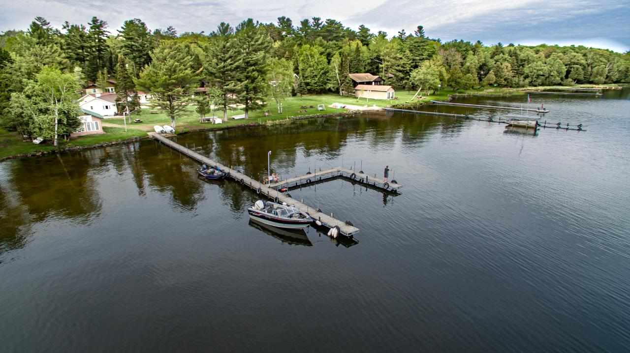 The ultimate venue for a family or corporate retreat on 4370-acre Lac Vieux Desert! 23 bedrooms and 11 bathrooms provide room for a large group to experience Northwoods fun together on the lake! There's eight units, a recently built waterfront recreation room, fish cleaning house, workshop plus a lovely 4br/2ba main home w/finished walkout basement, two kitchens, 3 season porch and 3-car attached garage. Everything needed to get started is included: 7 boats, motors, equipment, inventory, 2 ice shanties, supplies, linens, furnishings, etc. Many recent improvements include a new septic system for Cabins 1-6, new furnace/central a/c in main home and much more! Sellers will consider a land contract with $450K down or a 1031 exchange. Corporate retreat, family compound, church retreat, split into condominiums, or continue to operate as the profitable and well-loved Wind Drift Resort business--the choice is yours. Book a showing today!