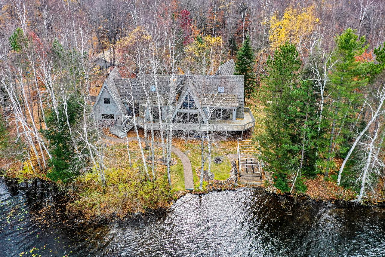 """Expanded and modified """"A-Frame"""" home, on a desirable three lake chain with level lot located quite near the sandy shore of Lower Sugarbush Lake. There is a massive double-sided fieldstone FP in both the dining & living area all open to the kitchen. Glass galore, master suite w/soaking whirlpool bath, separate granite shower & 3 season porch at lakeside. There are 2BRs & a shower bath up, along with a 14x27 bonus rm. The LL family room features a large wet bar, poker room, fieldstone FP, another BR a """"Loon"""" bathroom w/granite shower, laundry room w/utility area & granite flooring throughout. Add'l amenities include a huge deck at lakeside, att'd gar., detached 26x40 gar., 14x24 A-Frame storage bldg, blacktop drive & 48 acres of land, including a separate buildable lake lot & your own boat landing. The land includes the home on its own lake lot, an adjoining separate, buildable lake lot, and 3 other parcels purchased for privacy that are presently enrolled in MFL""""closed""""."""