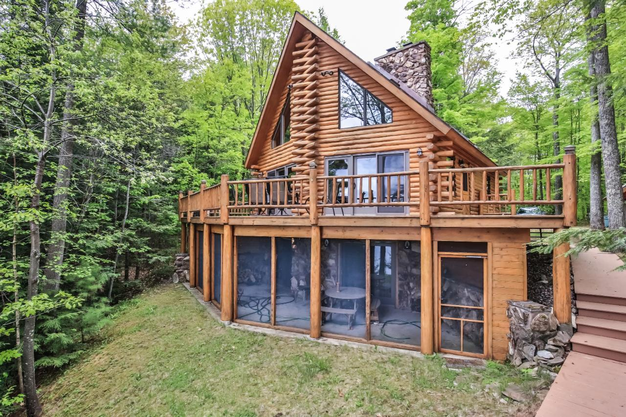 Spectacular private setting with towering pines on a dead-end road. This year-round log Chalet is western facing on Fence Lake and offers 125ft of perfect sand frontage, crystal clear water, over 3500 acres of endless recreation, a high end pier system, shore station and dry boat house with a party deck. The home is complete with 3 bedrooms, 2 baths, 2 wood burning fire places, a full wet bar and extra large screened in porch, A/C and a wraparound deck to enjoy cocktails and sunsets. More guest then expected? The 2 car detached garage offers a full bunk room that is insulted and heated. This property is pristine inside and out, is perfectly maintained and ready for a life time of enjoyment. Call to see this property and let your dream of Northwood's living come true.