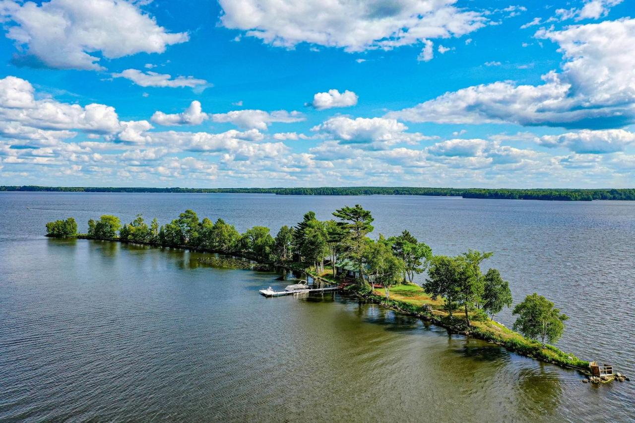Imagine owning your own private Island for a definite private getaway! On the market for the first time in 80 years. Swimming, boating, fishing, bird hunting, ice fishing on a 3500+ acre lake. This Pelican Lake Island with 1800 ft. of frontage is paired with a 1.2 acre buildable lake lot. The 2 bedroom, 1 bath cottage has all modern amenities: electric power, water, telephone, ac units, and electric heat. Recently remodeled kitchen and new bathroom. Cottage has metal roof, new deck, beamed ceilings and walls of windows. There is a wood burning fireplace in an open concept living area. There is an outdoor shower, fire pit area, sand swimming frontage and large trees. The Lake Lot has 100 ft. of frontage with 280 ft. of depth for plenty of room to build a year round home. It has a 2 car garage, western exposure, gentle slope to the water, beautiful sandy beach for swimming and provides for easy island access.
