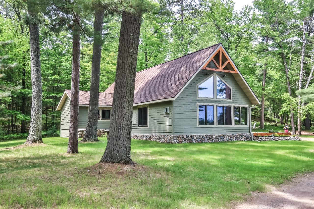 Perfect privacy on the Minocqua Chain. 27 acres with 1750 feet of frontage 4 minutes from downtown with no road noise. Towering trees with a half mile view and bordering the Minocqua Country Club. The home was completely remodeled with an addition of a great room. 30 year cedar smart siding with top of the line Kolbe and Kolbe windows, trex decking and patio and a full sized fenced in tennis court. The great room offers a wall of glass, hand scraped hickory floors, endless views and a floor to ceiling field stone fireplace. The new kitchen offers custom cabinets, slate appliances, solid countertops and is completed with a showpiece granite island. The master suite supports a large walk-in closet and a full bathroom with double sinks and spa grade shower. 6 berth pier system for all the toys and golf cart access to the Minocqua Country Club or a public sand beach completes this one of a kind package.