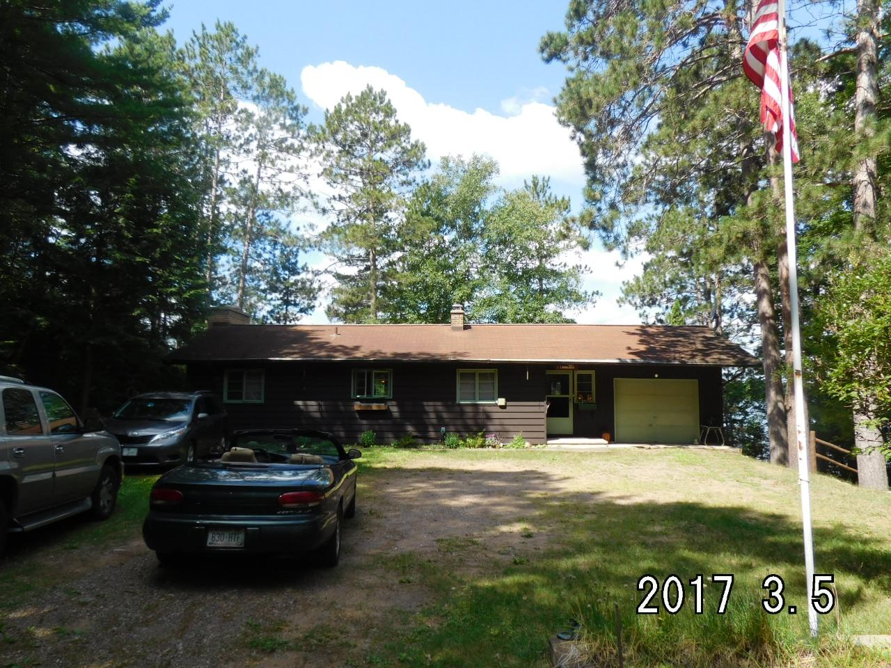 Looking for privacy on Big Water? This 3 bedroom 2 bath house with fireplace and attached garage sits in the middle of 365' of frontage with sand beach, western exposure and almost 6 acres of privacy. Walk out your lower level onto the deck of your 28x22 dry boathouse.Outbuildings included are a barn with workshop and an additional storage shed.