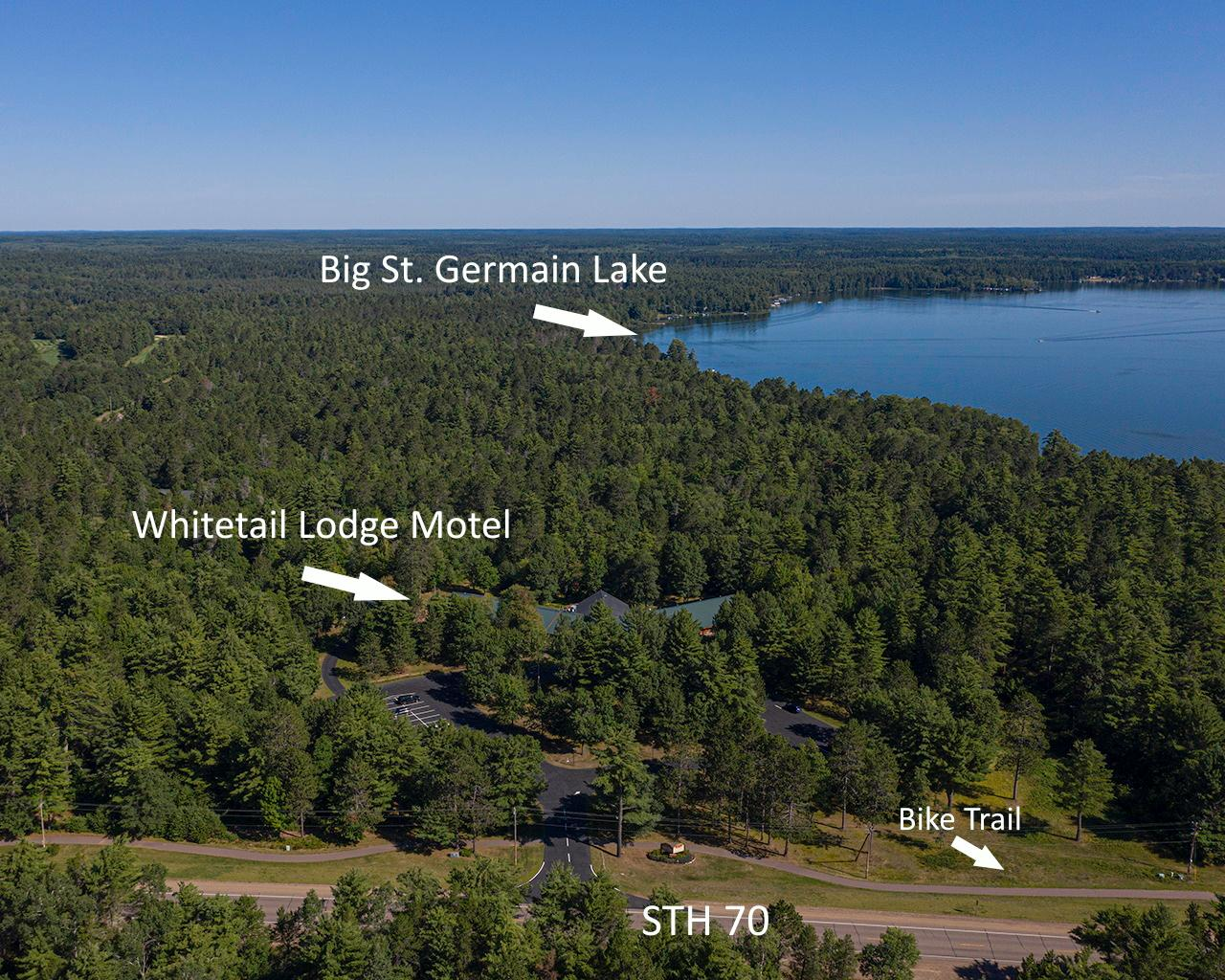 WHITETAIL LODGE MOTEL-Ideal successful business for the family that desires to live & work in the beautiful Northwoods of Wisconsin! This newly stained cedar lodge w/ metal roof is located on the outskirts of St Germain & near many quality lakes on 18+ wooded acres. 30-rooms, w/attached 3-BR, 2-BA residence, heated indoor pool, a jacuzzi hot tub & an exercise room. The lobby has 2 sitting areas & a massive stone gas FP. Direct access to the hiking/biking/snowmobile trail system & walking distance to the St Germain Golf Club, as well as superb nearby dining choices. The lodge is being sold turnkey, (incl a newer John Deere tractor w/cab & snowblower & a 2020 Ford F250 pickup w/plow system) & offers high speed Internet. Large, freshly sealed blacktopped parking lot, 3-car heated garage w/overhead storage, spacious yard for outside activities & varying room layouts, some w/FP's. Room for expansion! This is a manageable, profitable investment awaiting it's new owners! Whitetaillodge.com