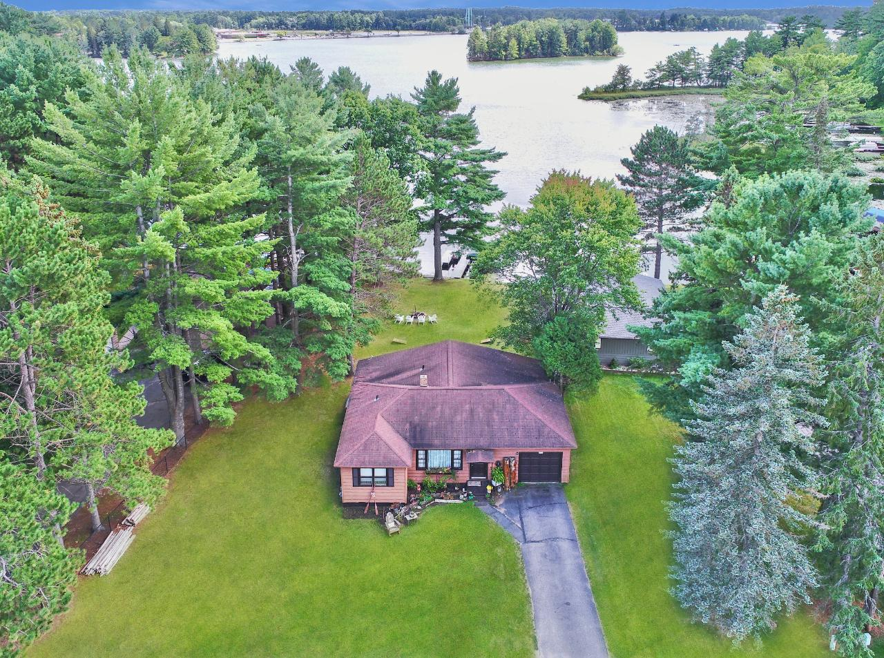 """Cozy cedar sided 2 BR, 2 BA home located on the much desired Minocqua Chain. This ranch-style home features 2 BR, 2 BA on the main floor, updated kitchen, new flooring, and an attached garage. The basement is unfinished and you could make what you'd like of it and add more finished sq footage. You can't beat this location with the option to walk or bike to town and hop on the Bearskin Trail! This home has ZERO steps to the lake and is pancake flat with southern exposure. There is a large yard with plenty of space to play bags, entertain, and enjoy your hot tub overlooking the lake. Enjoy the """"chain life"""" by boating to many bars and restaurants, watch the weekend water ski shows, or tie up to many of the state islands this chain as to offer!"""