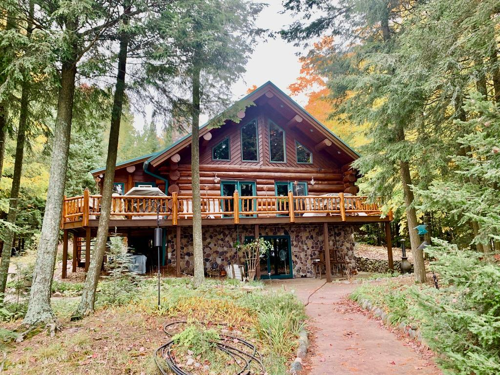 Full log luxury on the Northwoods finest lake. Butternut Lake is almost 1300 acres and over 75% of the lake is Nicolet National Forest. The 3+ bedroom, 3 bath home is in impeccable condition. It was built in 2001 by Ojibwa Builders and is full horizontal log and offers 2800 Sq. Ft. 100' of perfect south facing sugar sand frontage awaits you. The elevation is level and the views are extraordinary. Some features include cherry floors and cabinets, granite counters, walk-in shower, whirlpool, sauna, a second kitchen in the lower level, a magnificent wood-burning stone fireplace, lake side deck, sun room and fully finished walkout lower level. There is also a detached 2+ car garage. The landscaping is terrific as well. The home was stained in 2020 and there is a metal roof. The home is being offered turnkey. Almost all furnishings and the pier (a gorgeous new Porta Dock) are included! This is one exceptional home and it is on an extraordinary spot and lake!