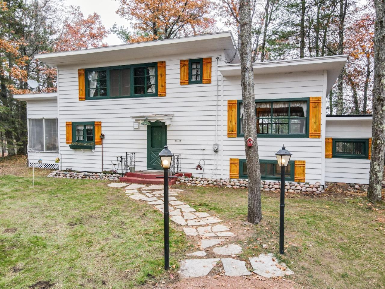 Northwoods Elegance. This historic Northwoods charmer has yesteryear character with modern day amenities. This park-like setting offers crystal clear water and sand frontage. The big water views include islands, peninsulas and mostly undeveloped shore lines. The property supports towering pines and mature oaks with a new circle drive and a three-car garage. The great room features 20ft ceilings, lots of glass and a field stone fireplace. The walls are finished with a knotty pine golden glow and towering French doors leading to the oversized screened porch. A true gem with priceless views. Complete this package with 3 spacious bedrooms and a full basement. Located on the sought-after Crawling Stone Lake on the Fence Lake Chain of Lakes. Charm and location like this won't last long.