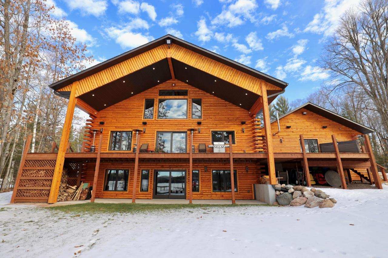 Spectacular one of a kind property with western sunset views on Birch Lake. This 4 BR, 5 BA home checks all of the boxes with regards to upgrades and high end finishes throughout. On the main level you will find an expansive kitchen featuring granite, Sub-Zero/Wolf/Bosch appliances, custom cabinets, living room w/ 22' cathedral poplar ceilings, gas FP, master BR w/ ensuite, & 2nd BR. The walkout basement is fully finished which houses the rec room w/ wood burning stove, 2 additional BR, 2 full BA, & laundry/utility room. The 2nd floor finished loft (est. 510 sq ft) can be used as a 5th BR, office, or family room and also has a 1/2 bath. This home has an unbelievable outdoor spread with huge lakeside deck which leads to the level approach of 266' frontage on full rec Birch Lake. There is a large heated & insulated garage w/ 10' overhead doors perfect to store your boat and toys! Located close to Manitowish Waters and the many trails for hiking, biking, skiing, & snowmobiling!