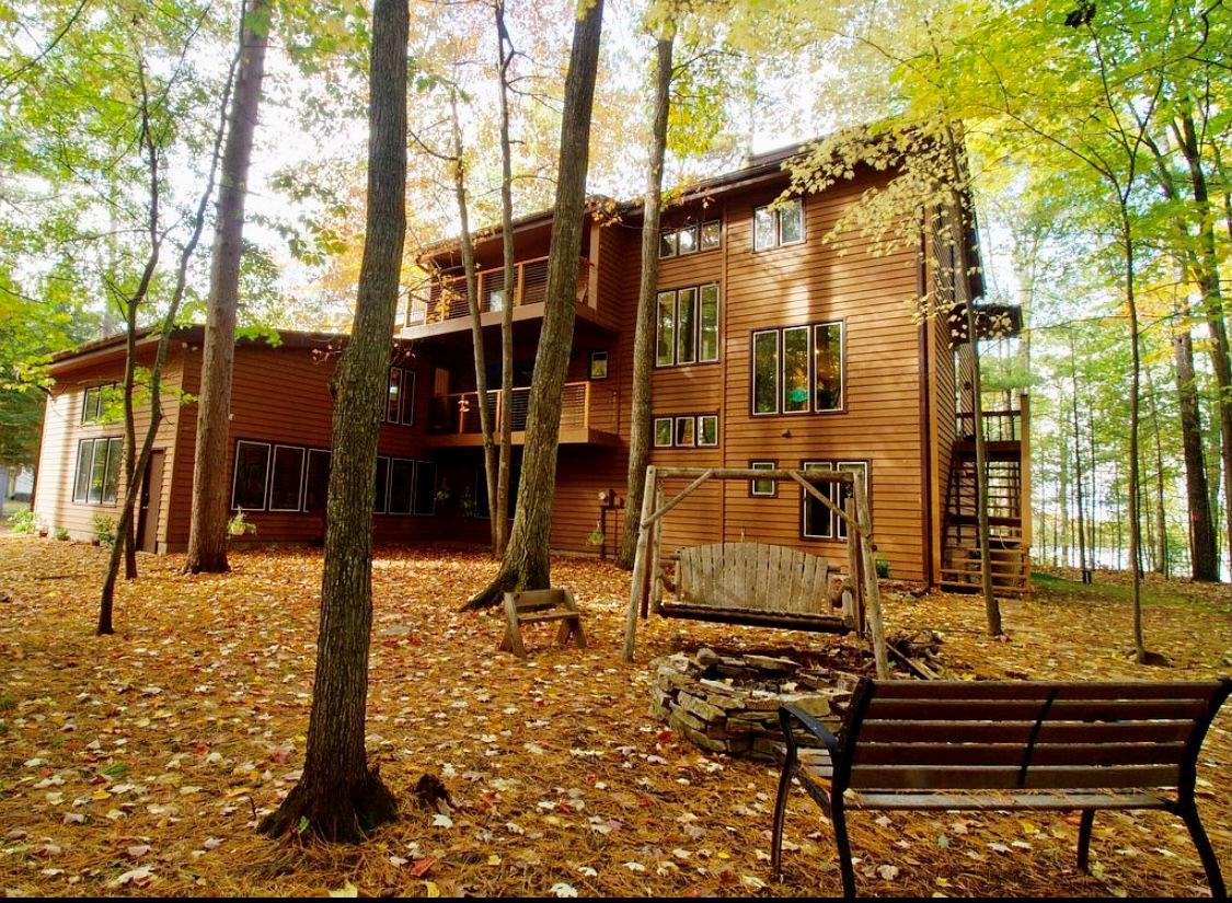 This large modern structure of stone, wood and glass is a Northwoods jewel set amongst mature trees, above 118 acre, full rec McCormick Lake. It has 4 bedrooms with 2 ensuite bathrooms, 2 additional bathrooms, plus 4 other rooms currently used as offices, toy rooms and exercise rooms. Recently remodeled in 2018, it's equipped with vaulted ceilings, 2 fireplaces, panoramic window views, a 2nd story wrap around deck, 4 car attached garage, a fire pit and a pier. It sits on 2.5 acres and has 150 ft of frontage! Don't wait long to make this oasis your own! The lake front view from this property is private. You do not see neighbors on either side other than driving in.