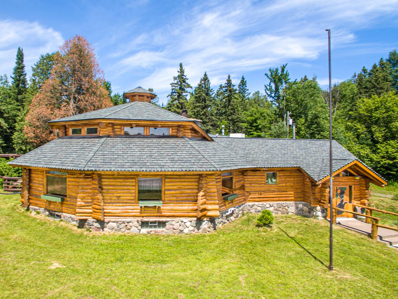 Imagine what you can do with this incredibly well finished full log masterpiece located on busy US-2. Over $700K invested in renovations and absolutely no expense was spared in terms of material quality from floor to ceiling. Could be used as an impressive business location, restaurant, rental lodging (there are 3 bedrooms downstairs along with a master bath), B&B, even a luxurious home, or whatever one can imagine. Situated on 11 acres with a huge pond, this property is located on US Highway 2 and is ready to use and enjoy now! Massive stone fireplaces, the finest quality finishes, wood carvings, a gorgeous bar, impressive loft, and incredible recreation area--no detail was overlooked! Just a couple miles from the best skiing in the Midwest, across the road from the snowmobile/ATV trail, and conveniently located right next to the medical center. One is sure to be impressed upon entering this property which is offered for a mere fraction of its replacement value...call today!