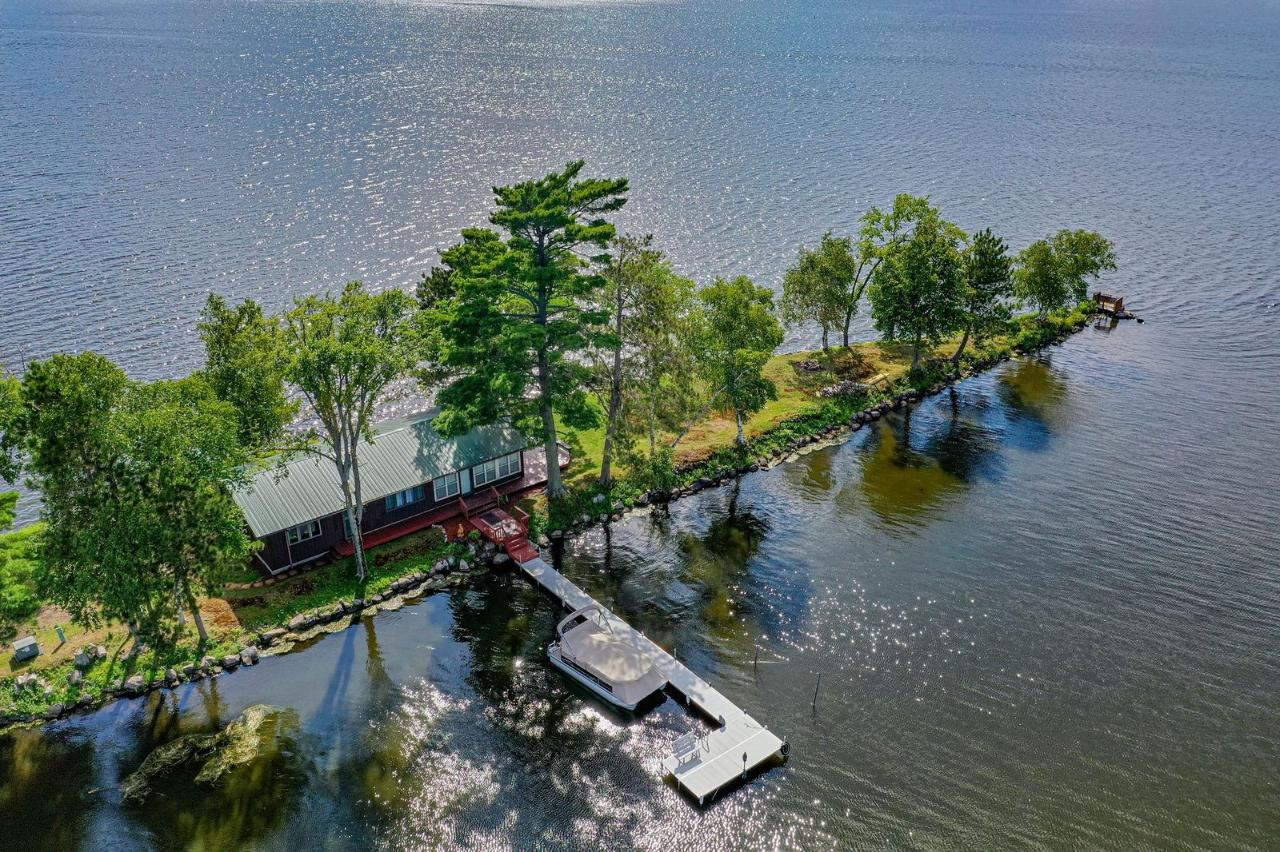 Own your own private island in northern Wisconsin! On the market for the first time in 80 years. Don't miss this opportunity. Swimming, boating, fishing, bird hunting, ice fishing, watching the sun rise and set all at your fingertips. A true norther Wisconsin gem full of relaxation. This unique Pelican Lake Island with 1800 feet of frontage has a cottage with modern amenities: electricity, water, telephone line, ac units, & electric heat. The two-bedroom, 1 full bath cottage is move in ready. Recently remodeled kitchen & brand new 3-piece bathroom. It has a metal roof, new deck, beamed ceilings & walls of windows to welcome the lake view in nearly every direction. There is also a wood burning fireplace. The kitchen has two breakfast bar areas to enjoy your morning coffee as the sun breaks the horizon. There is an outdoor shower, fire pit area, & sand swimming frontage. You can take in all the glory of the evening sunsets as the sky gets painted with color. Pontoon included